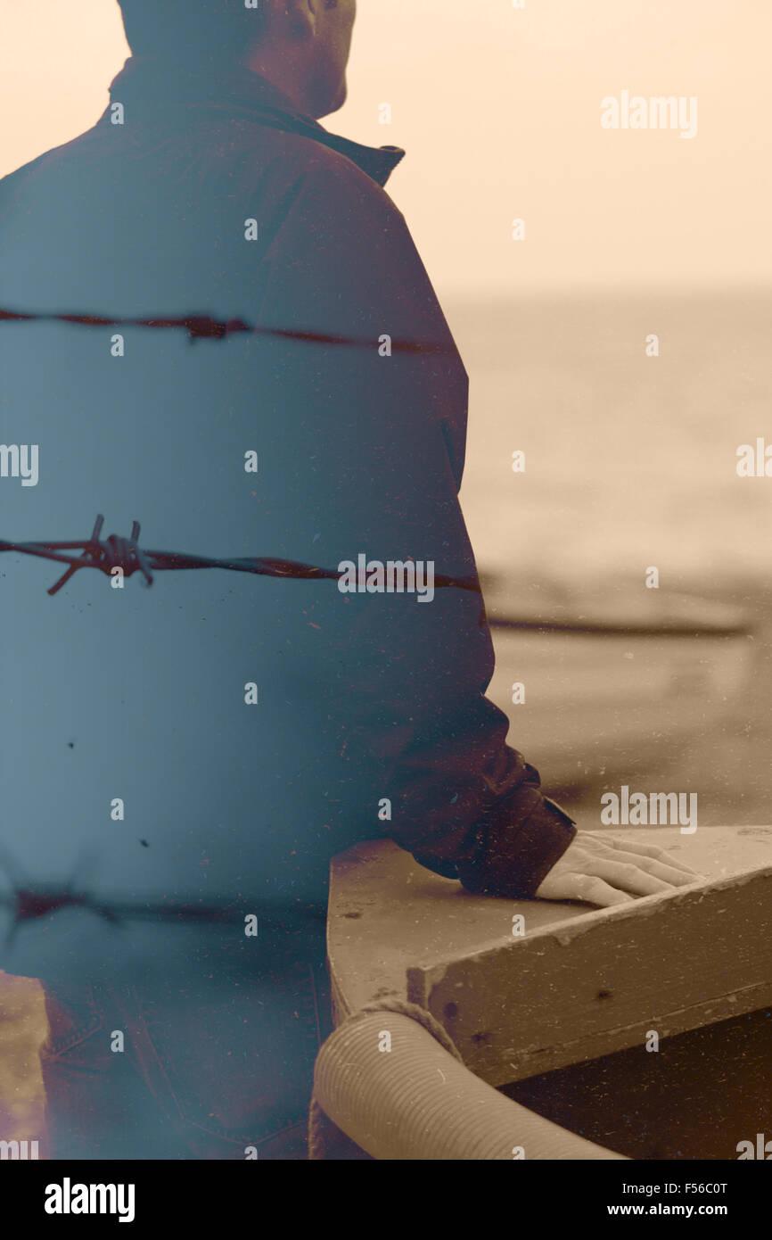 Doppia esposizione di un uomo e di filo spinato Immagini Stock