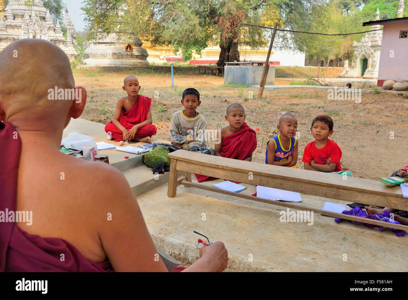 Monaco buddista di insegnare agli allievi le lezioni all'aperto nel parco di stupa e templi vicino a Mandalay Immagini Stock