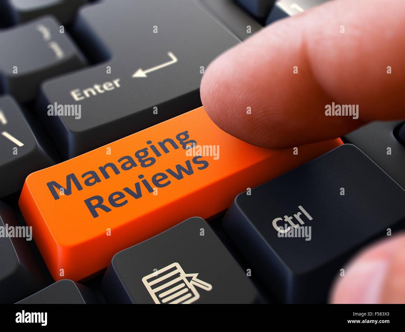 Un dito preme il pulsante arancione la gestione di recensioni su nero della tastiera del computer. Primo piano. Foto Stock