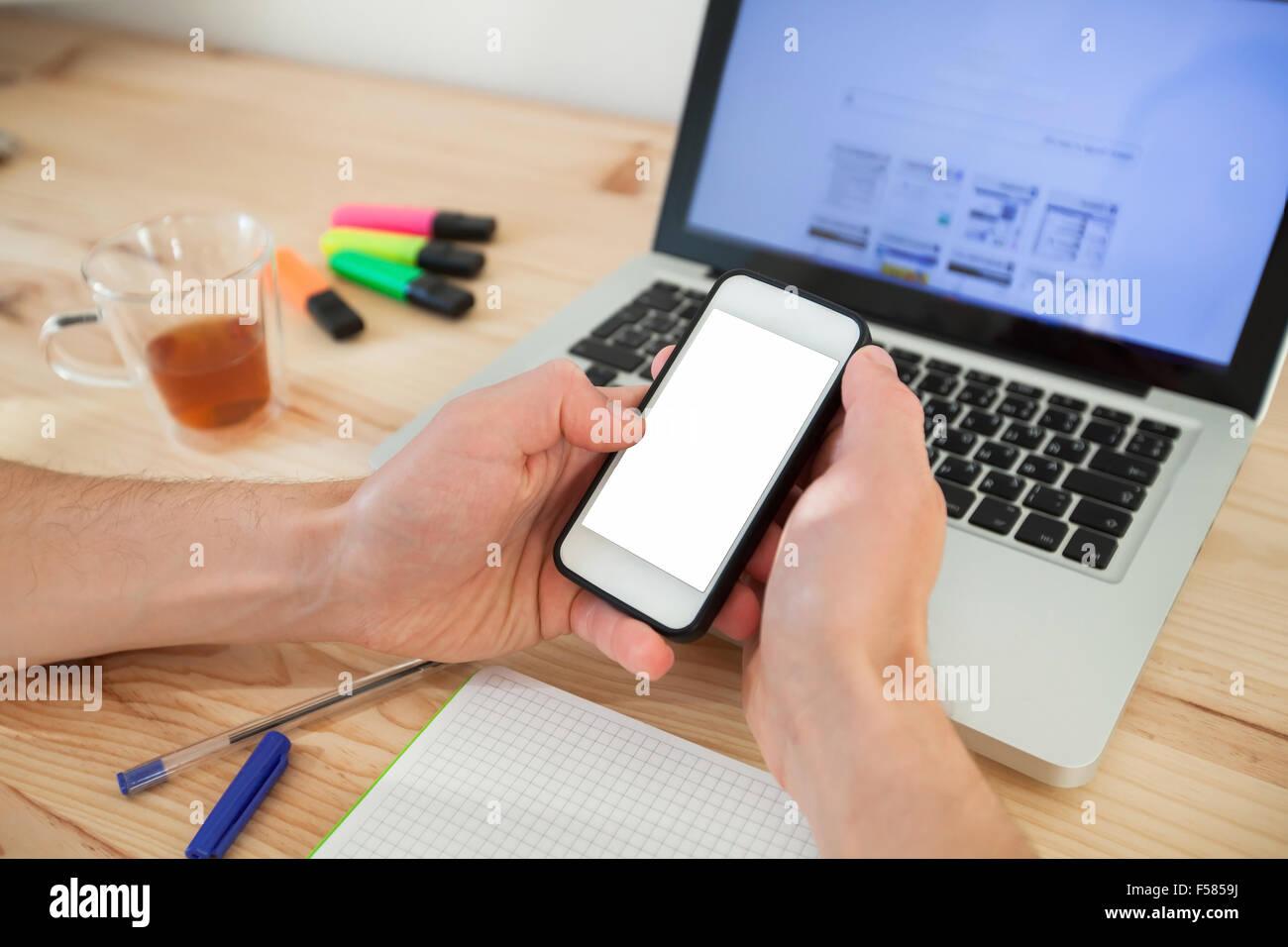 L'uomo utilizza lo smartphone con lo schermo bianco vicino al computer portatile in casa interno Immagini Stock