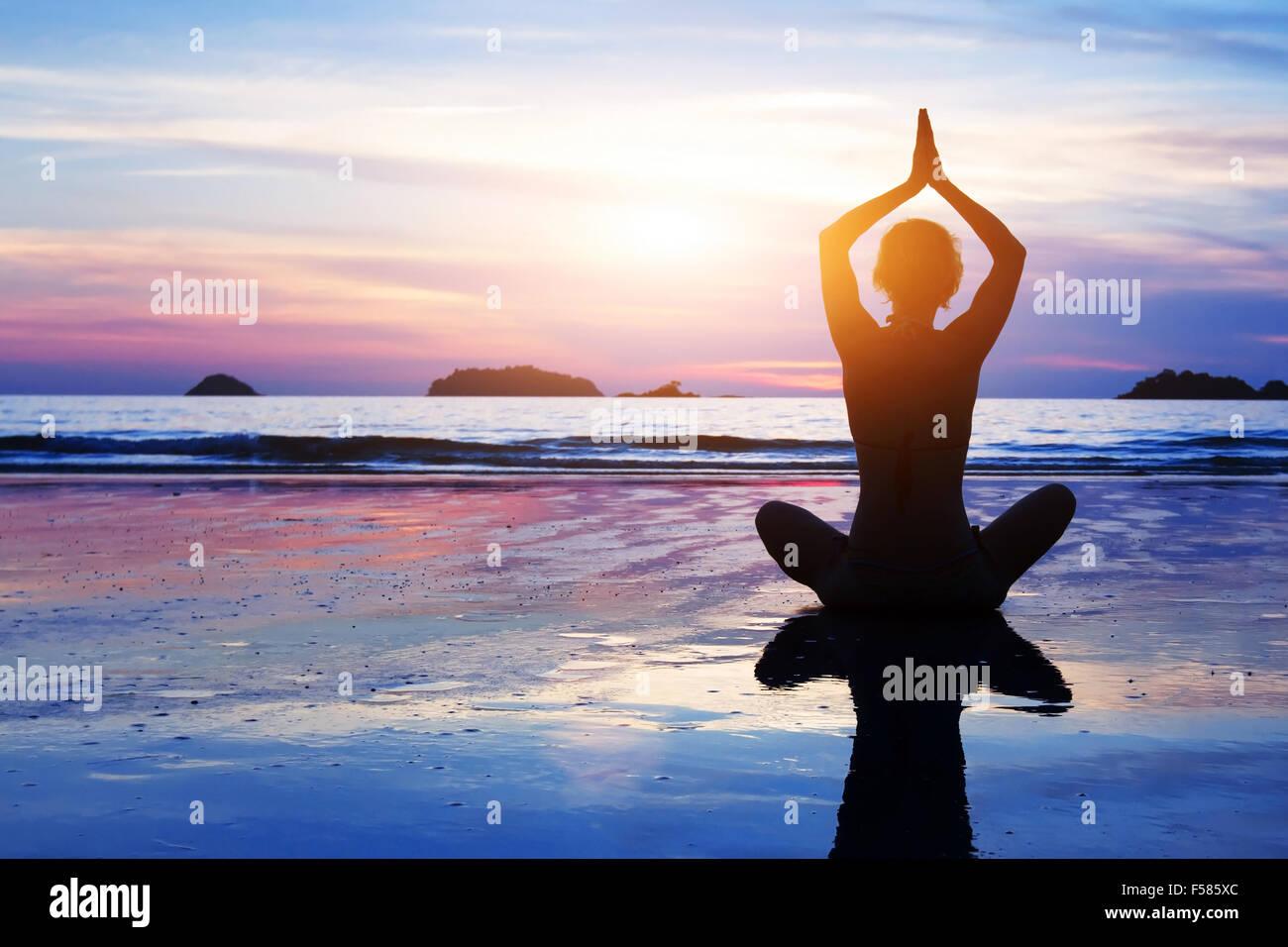 Sfondo di yoga, abstract silhouette di donna meditando sulla spiaggia Immagini Stock
