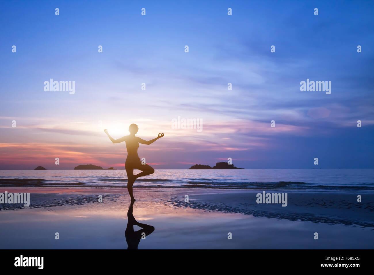 Lo yoga, silhouette di donna sulla spiaggia Immagini Stock