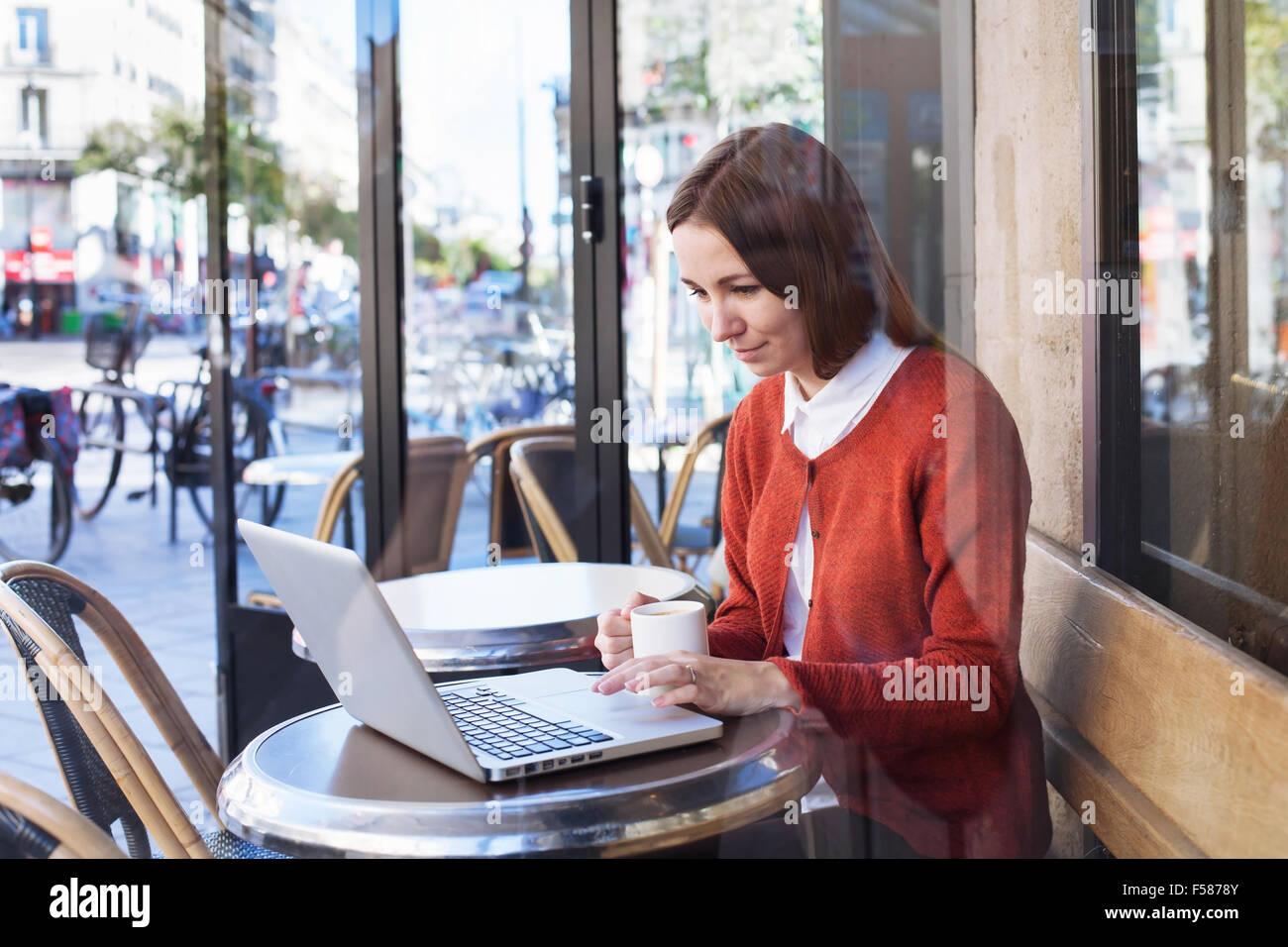 Giovane donna che lavorano con il computer portatile in cafe Foto Stock