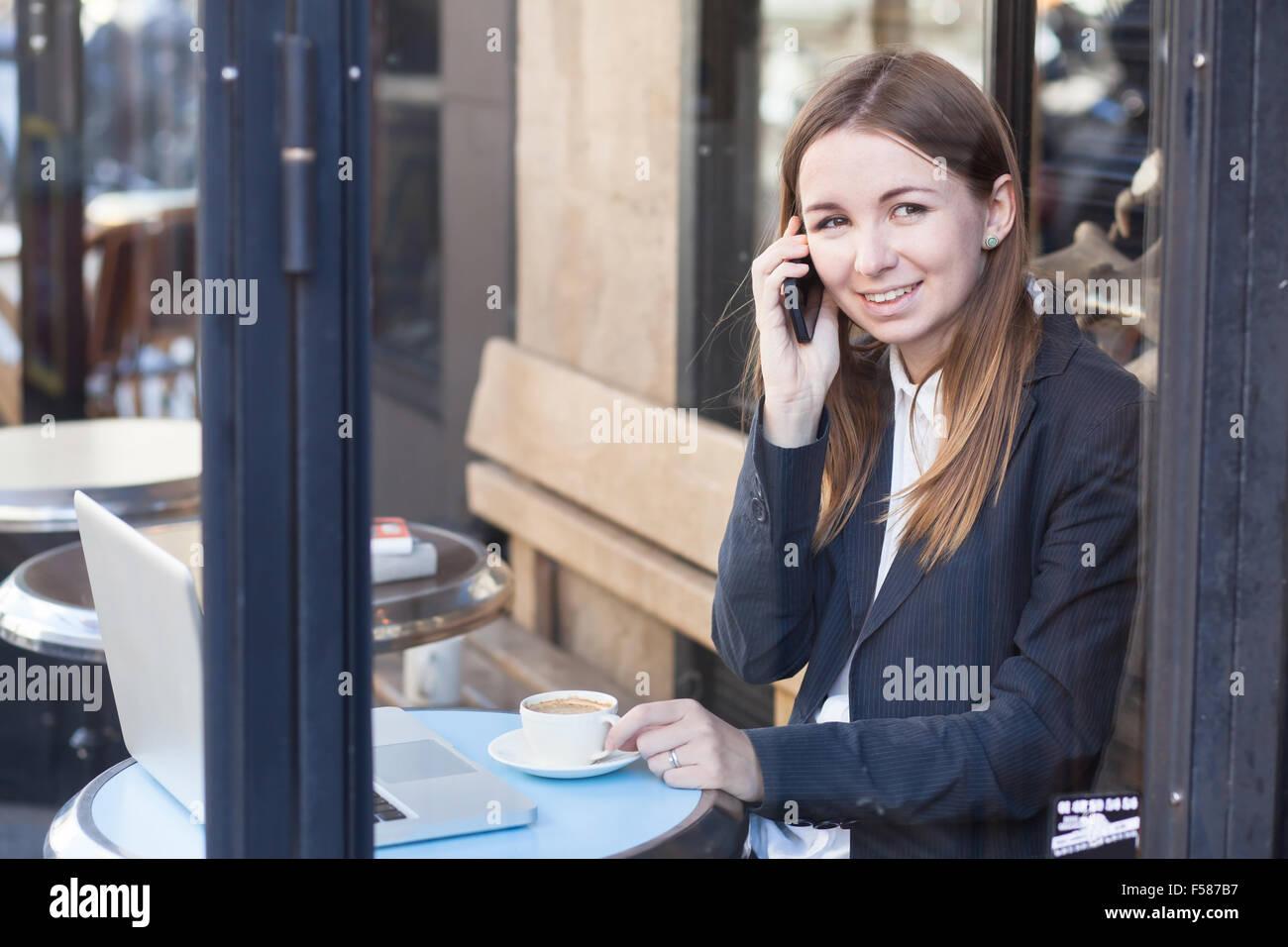 Sorridente business donna parla al telefono in cafe Immagini Stock