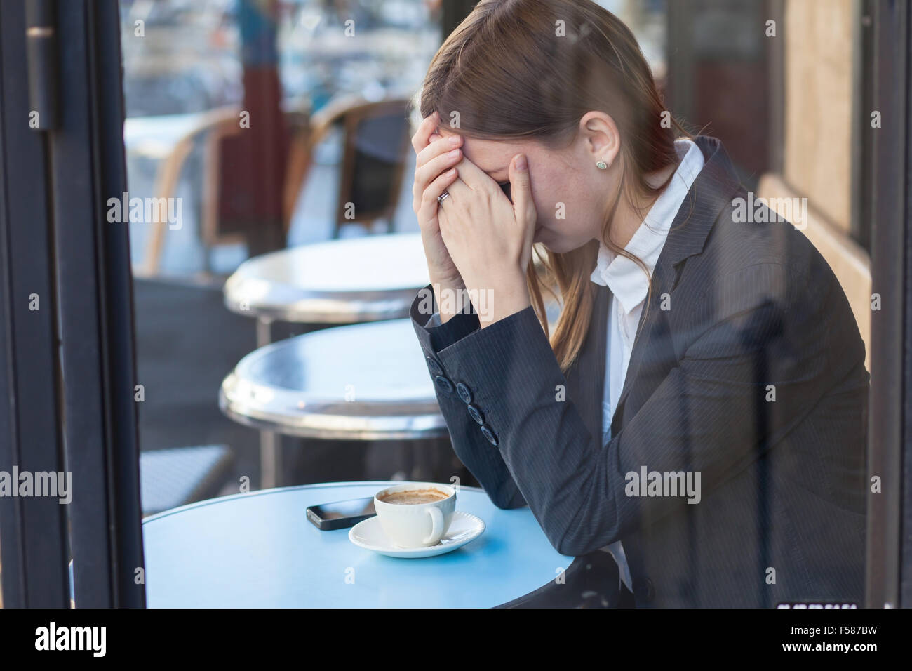 Donna che piange in cafe Foto Stock
