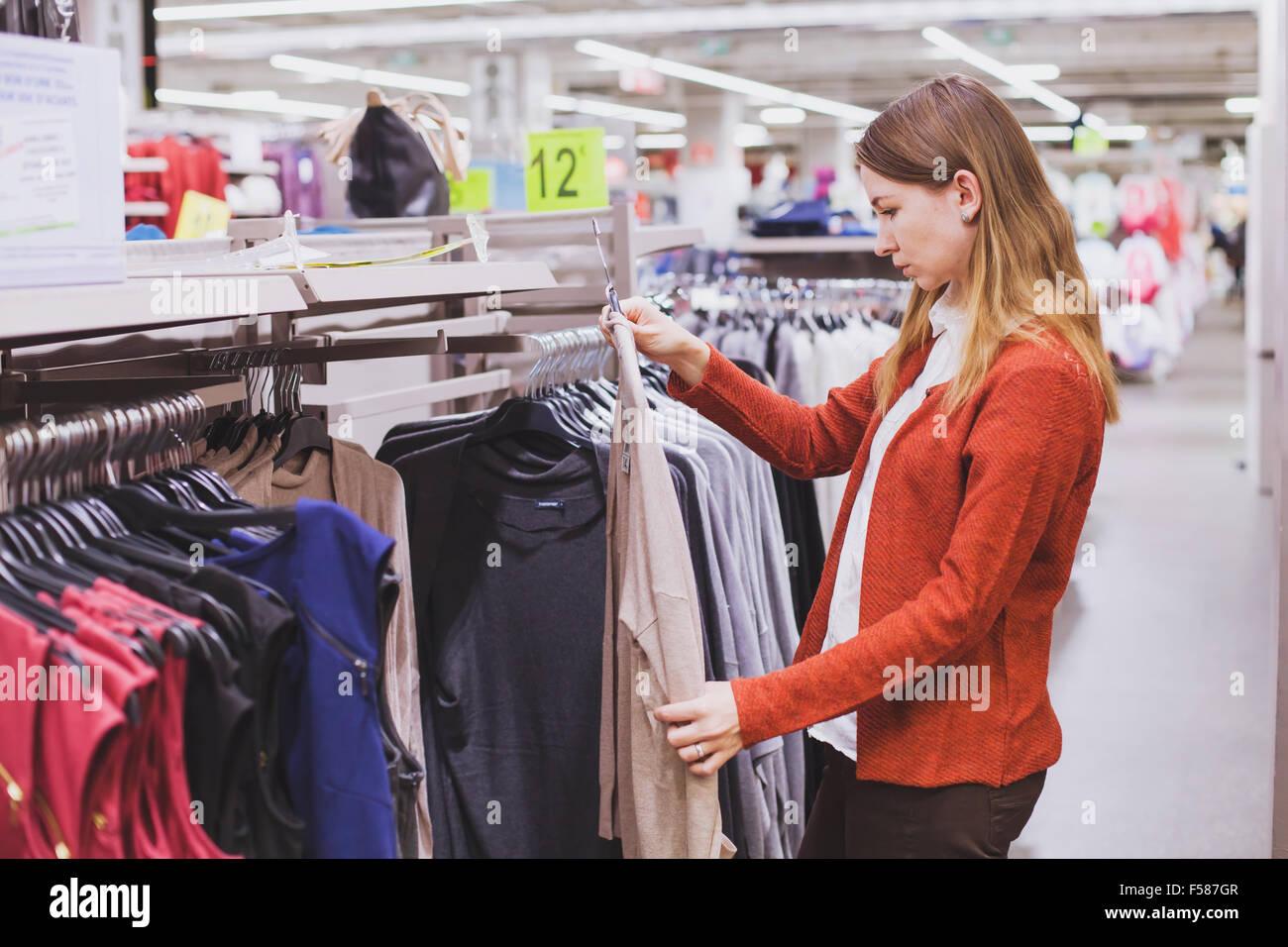 Donna scelta di vestiti in negozio Immagini Stock