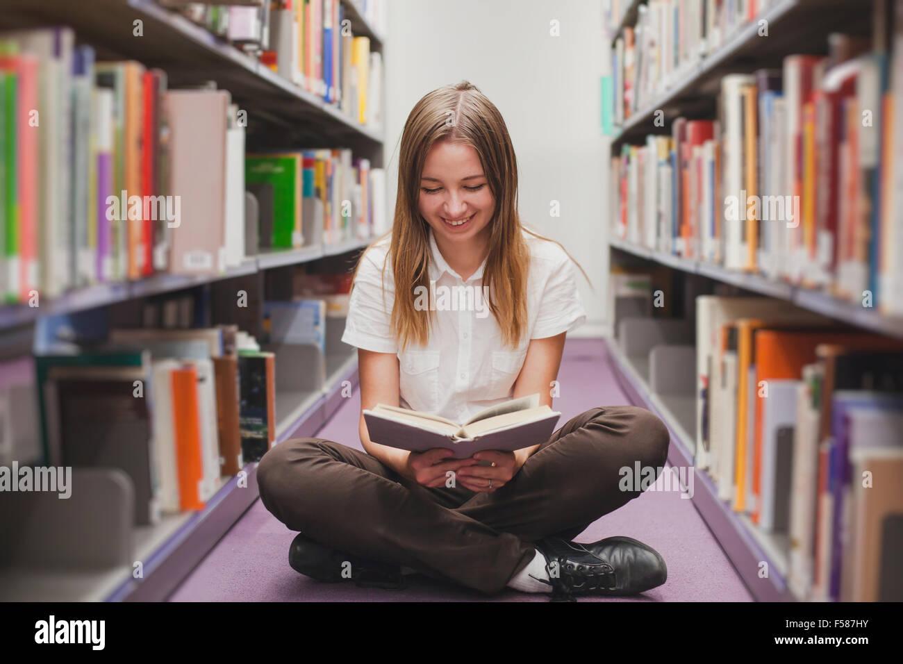 Lettura della ragazza in biblioteca, sorridendo felice studente Foto Stock