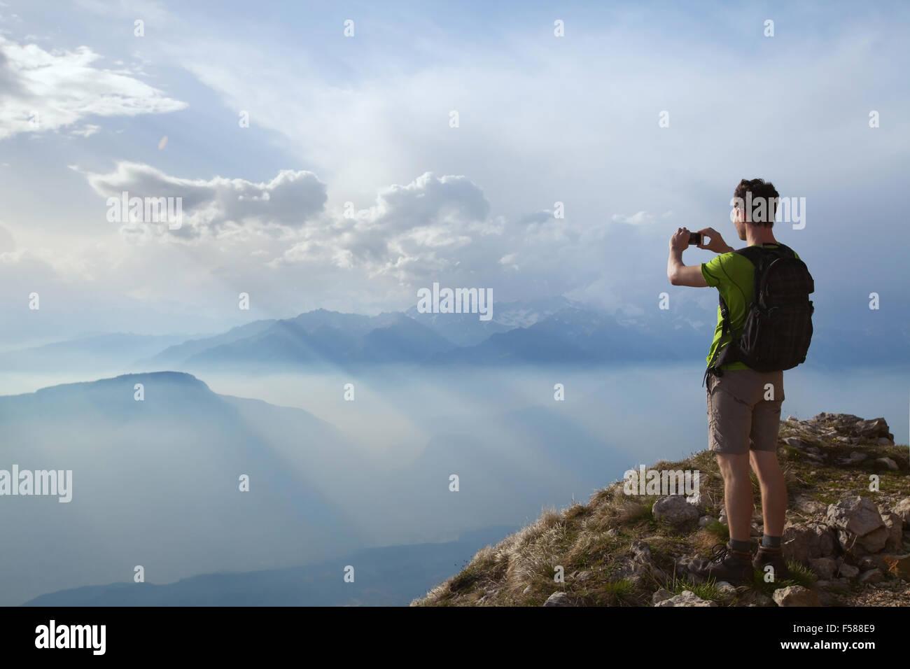 Escursionista tenendo la foto del bellissimo paesaggio di montagna con il telefono cellulare Immagini Stock