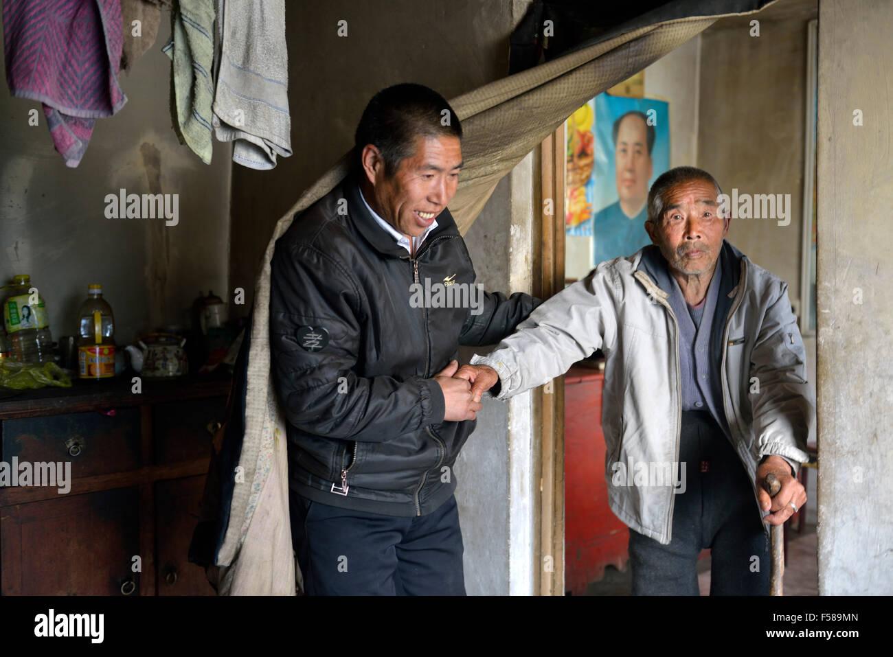 Wu Deyi, 48, che mai merried a causa della povertà, a sostenere il suo padre Wu Hai, 83, che soffre con atrofia Immagini Stock