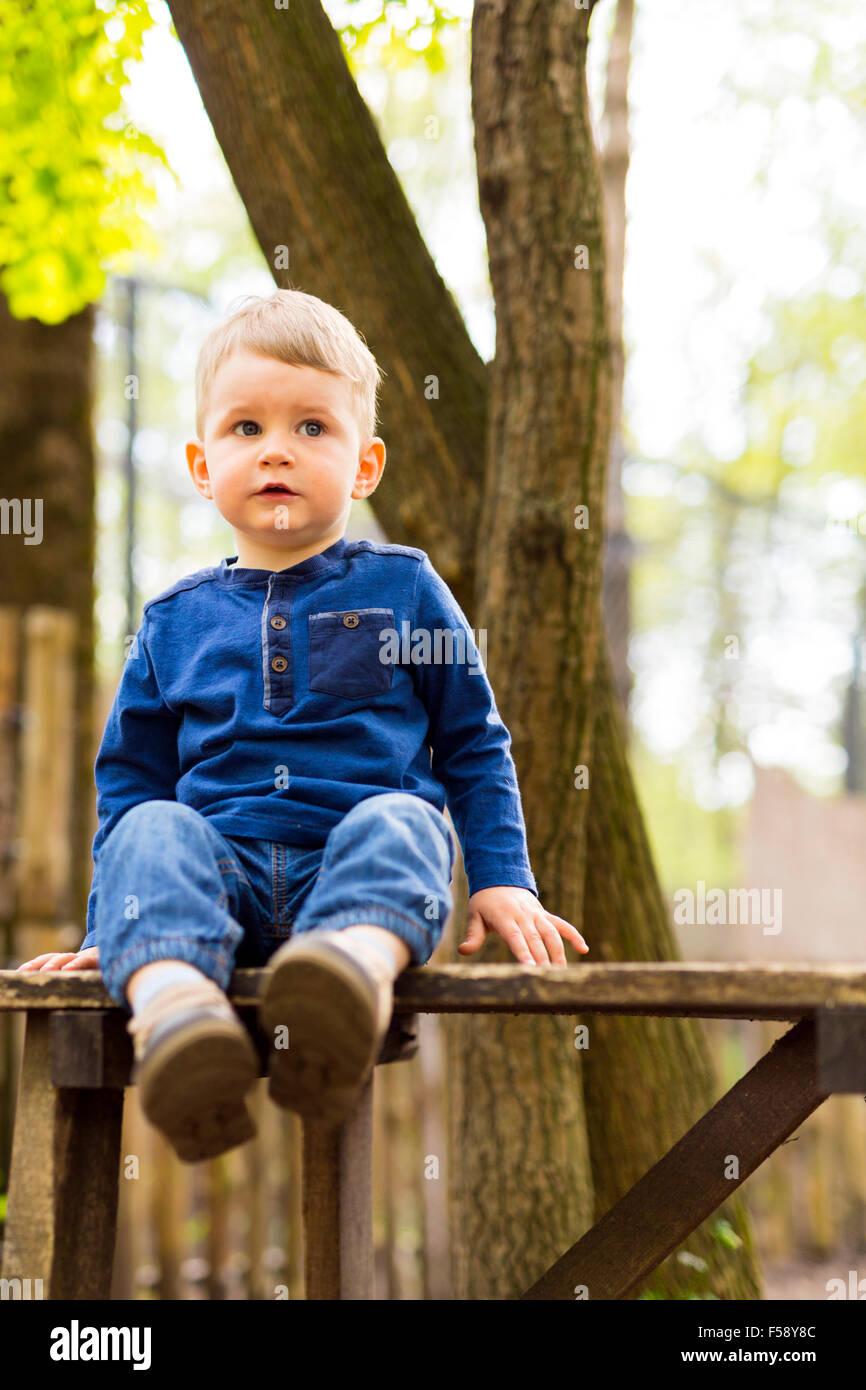 Poco bello ragazzo seduto su una panchina nel parco Immagini Stock
