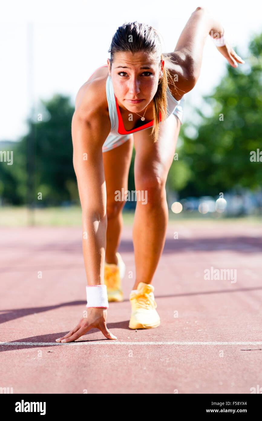 Bellissima femmina sprinter ottenere pronto per l'esecuzione durante l'estate Immagini Stock