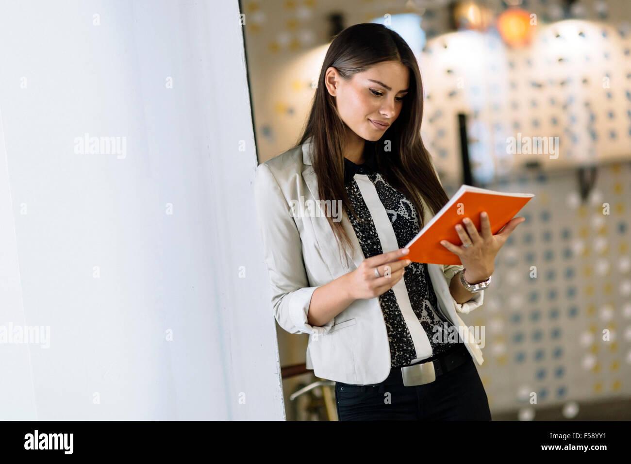 Imprenditrice la lettura di un documento in un ufficio moderno Immagini Stock