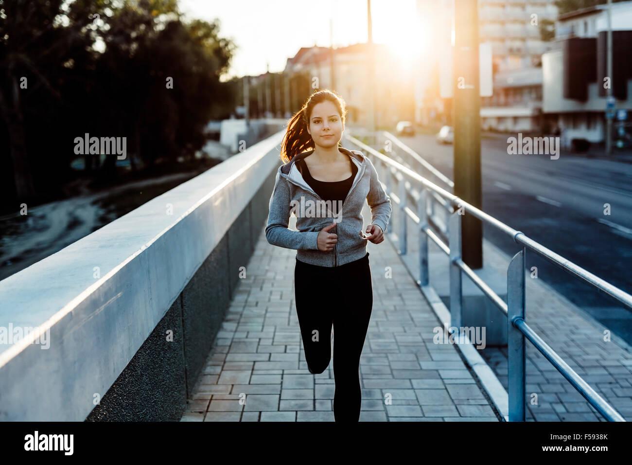 Bellissima femmina jogging in città e mantenendo il suo corpo in forma Immagini Stock
