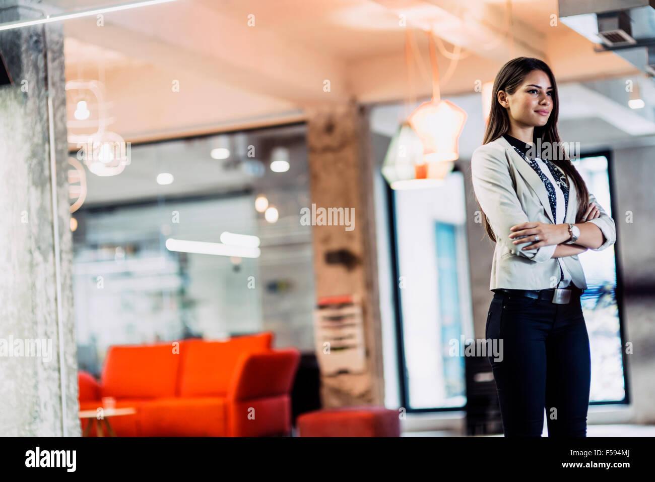 Fiducioso imprenditrice in piedi in ufficio con mani incrociate Immagini Stock