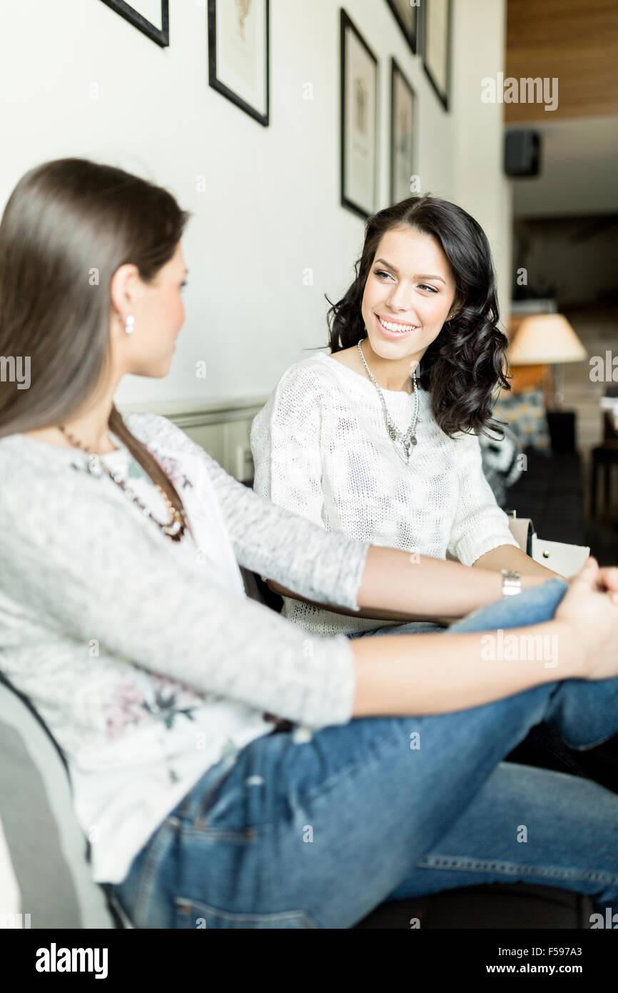 La giovane e bella donna avente una chat in loro preferito bar caffè Immagini Stock