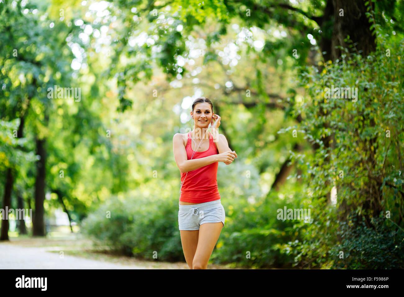 Giovane e bella jogging nel parco ascoltare la musica tramite auricolari mentre è in esecuzione Immagini Stock