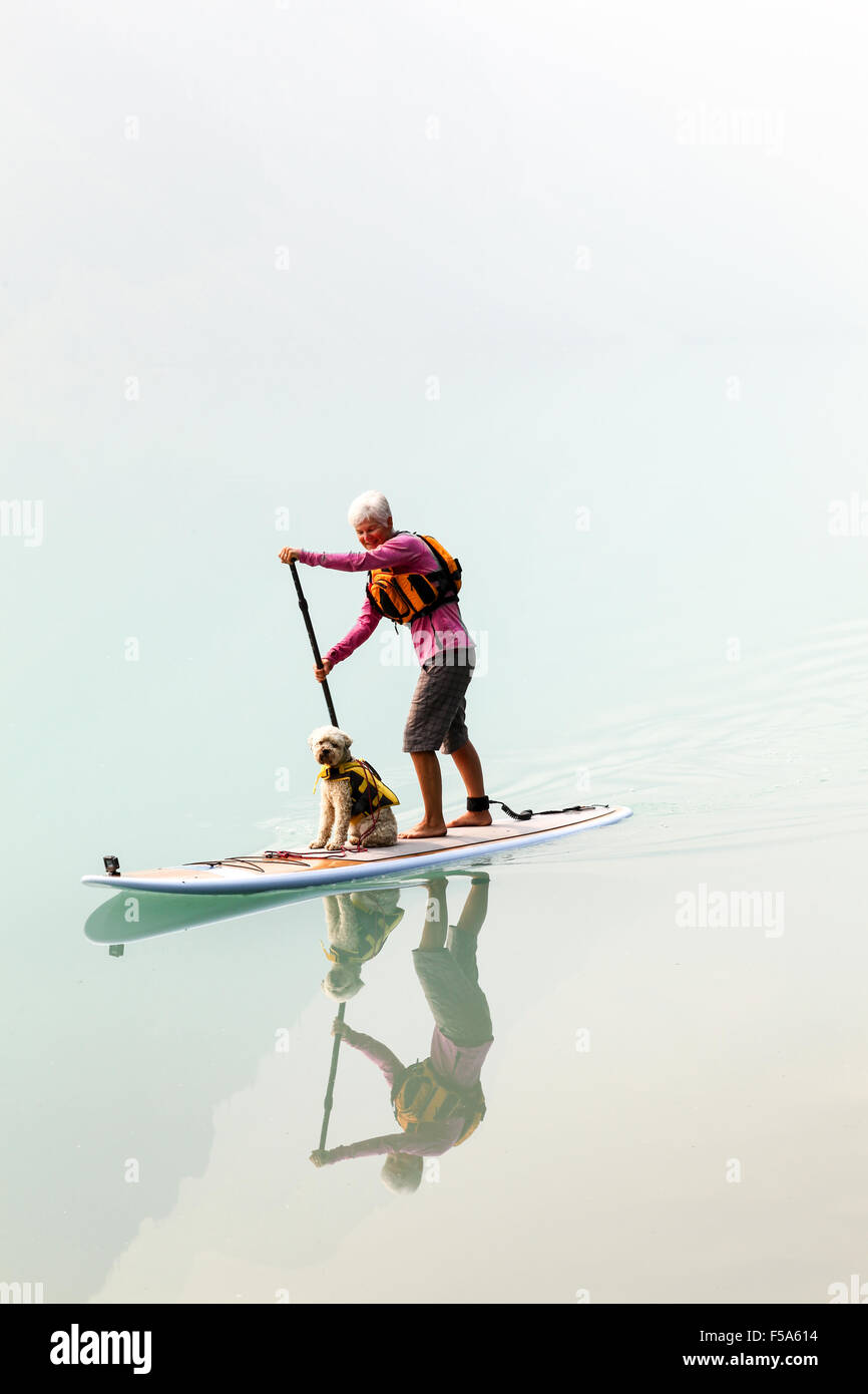 Una donna e il suo cane su un paddleboard sul Lago Louise e il Parco Nazionale di Banff Alberta Canada Immagini Stock