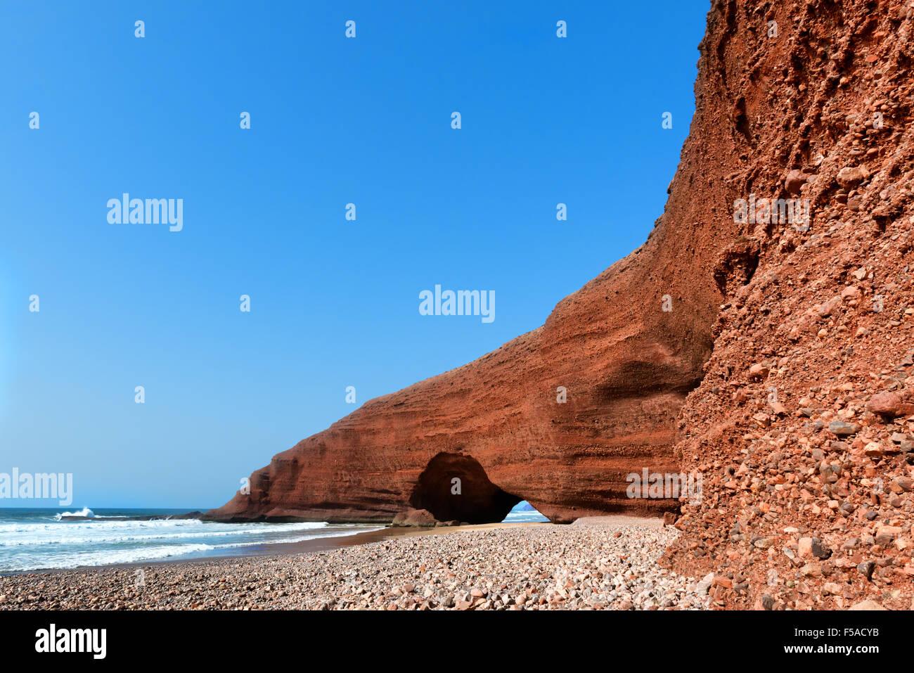 Naturale di mare-usurati archi di roccia contro il cielo blu e chiaro a Legzira beach, Marocco. Immagini Stock