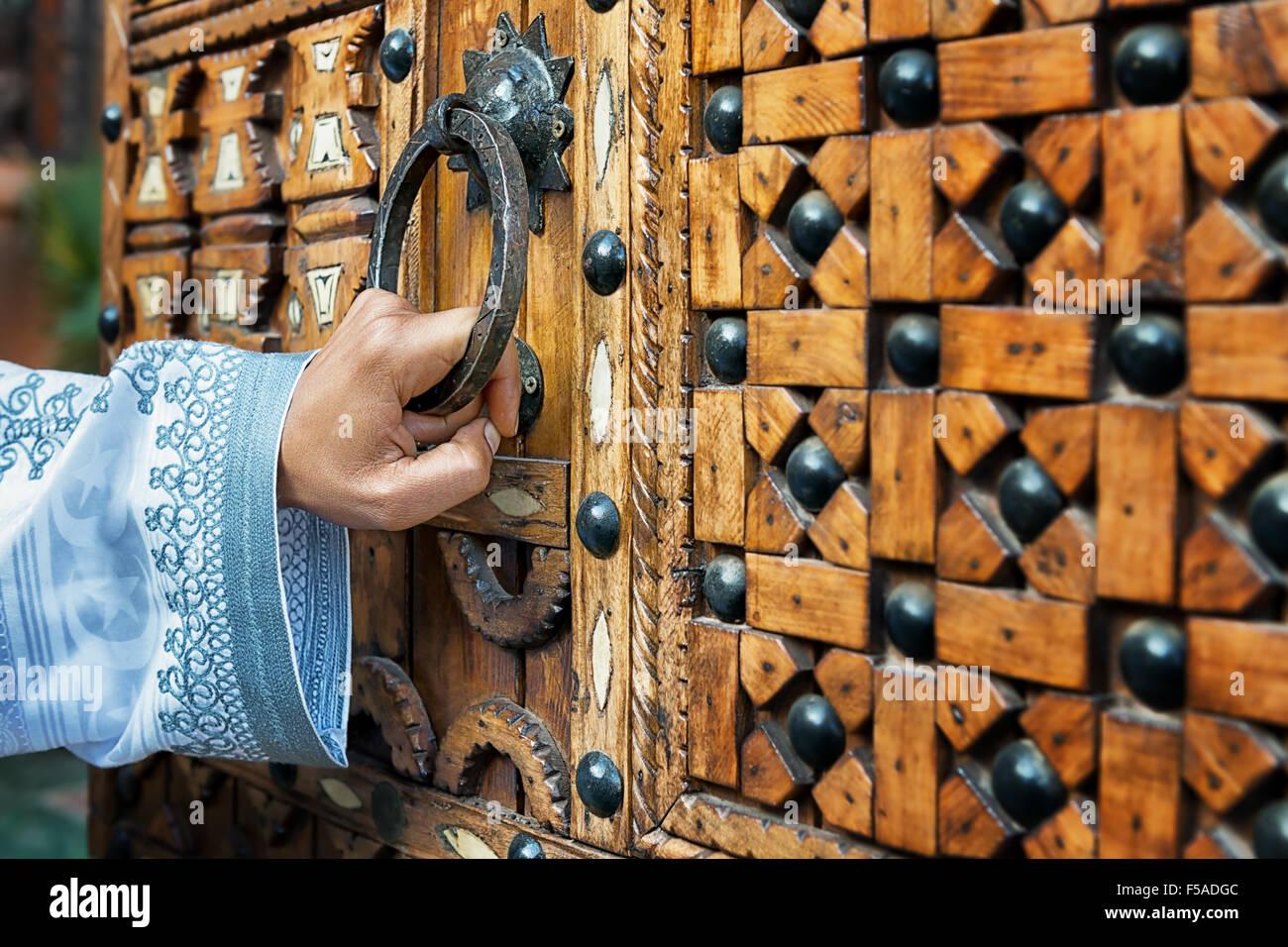 Una mano che tiene la maniglia di una porta di un tradizionale in legno porta marocchina, nel sud del Marocco. Immagini Stock