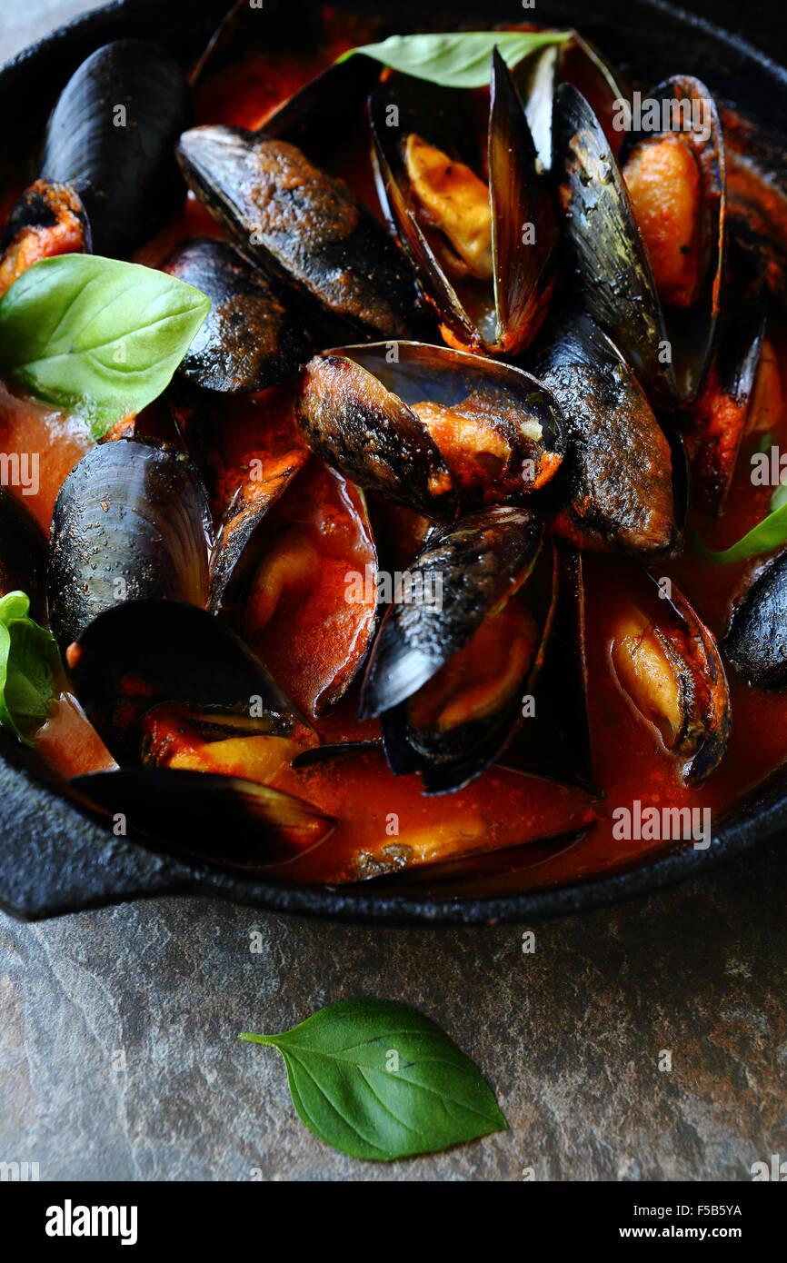 Le cozze in salsa di pomodoro con aglio, cibo closeup Foto Stock
