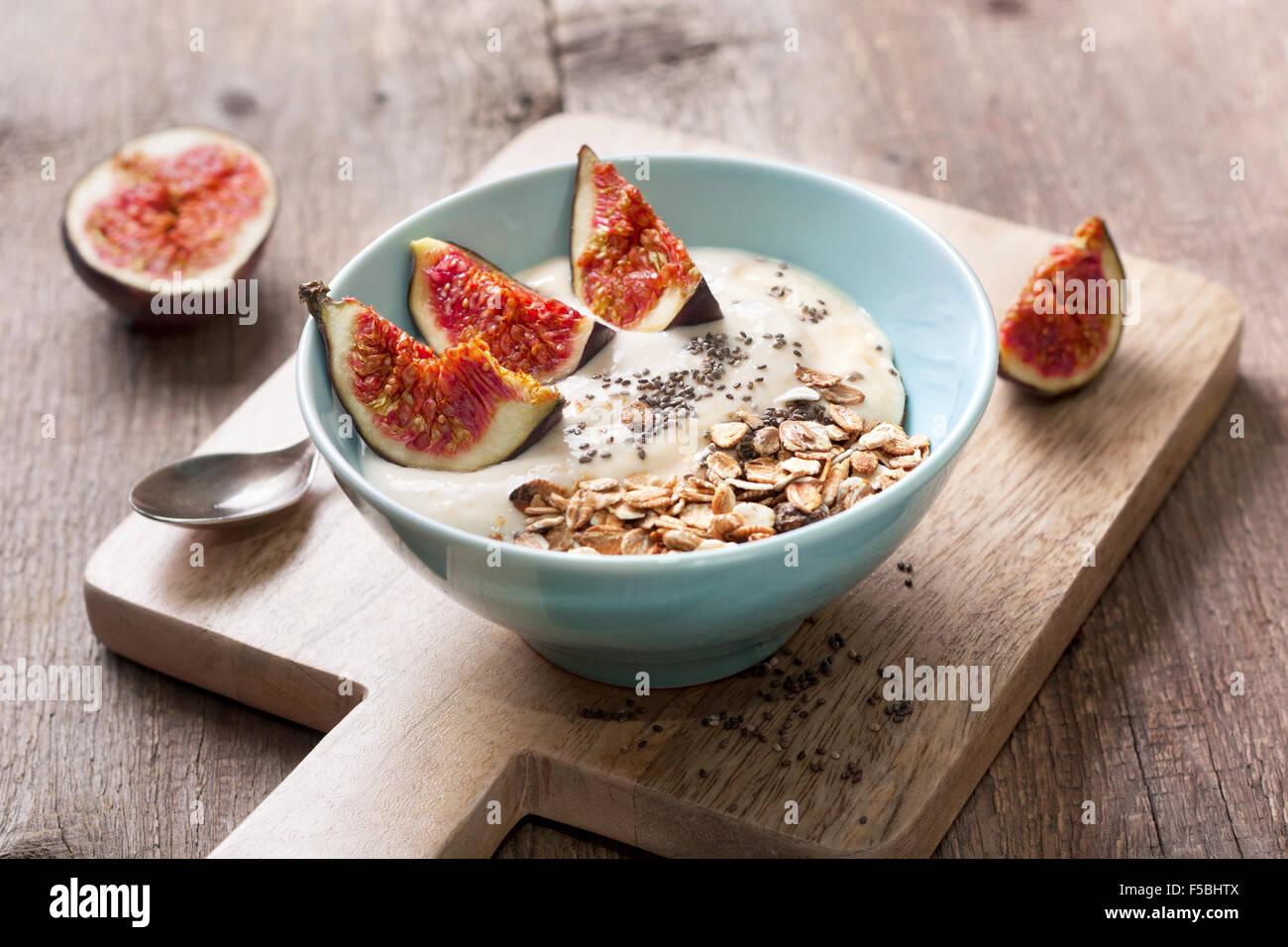 La prima colazione con muesli, yogurt, fichi e chia semi in un vaso blu su uno sfondo di legno Immagini Stock