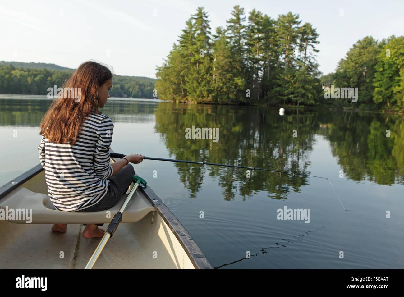 Ragazza giovane la pesca da una canoa su un lago calmo con alberi in background Immagini Stock
