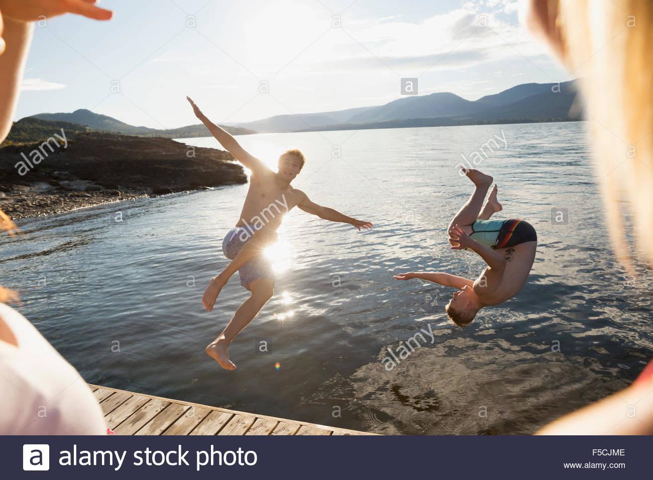 Le giovani donne a guardare gli uomini salto nel lago Immagini Stock
