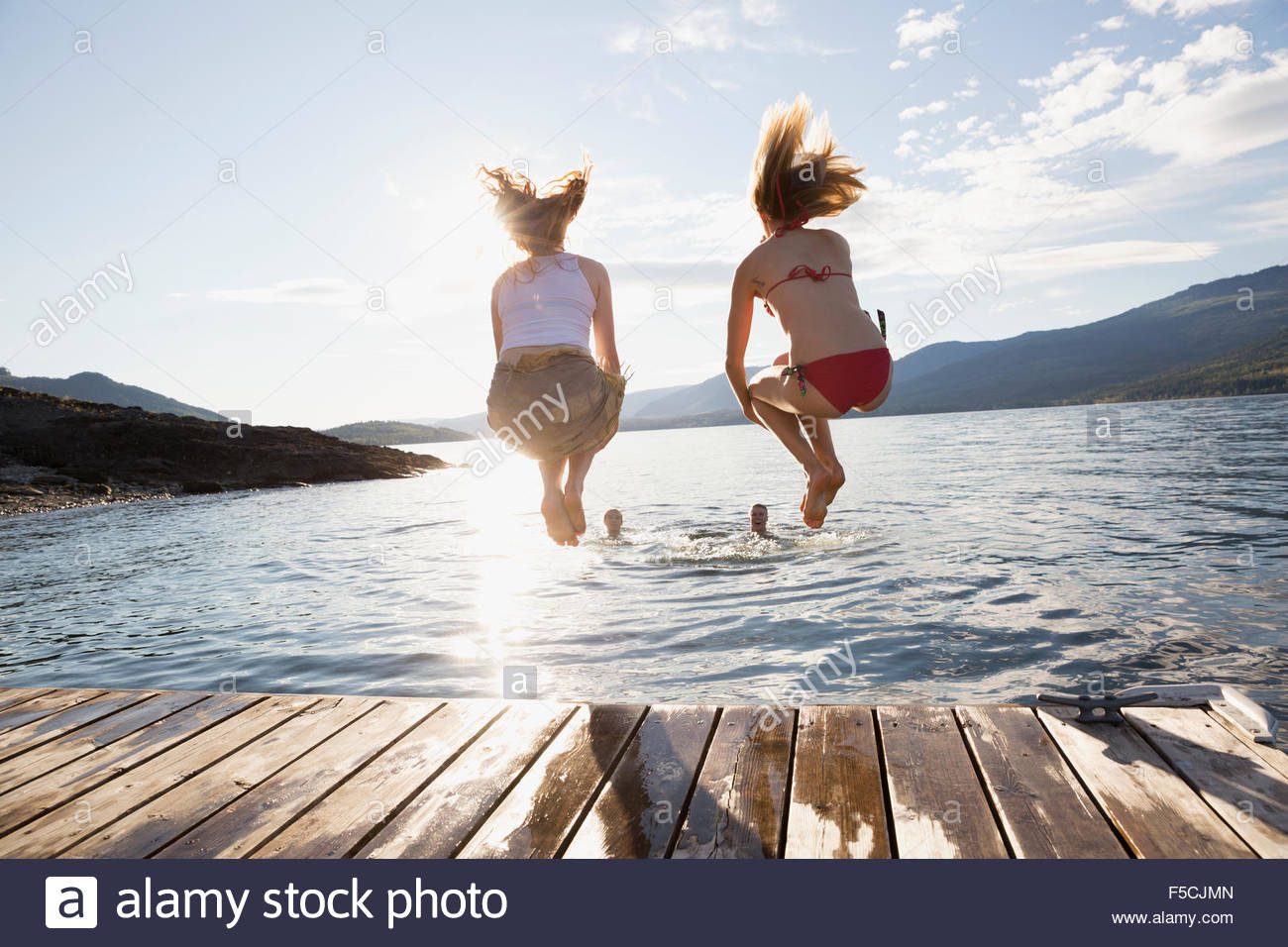 Giovani donne jumping dal dock nel lago Immagini Stock