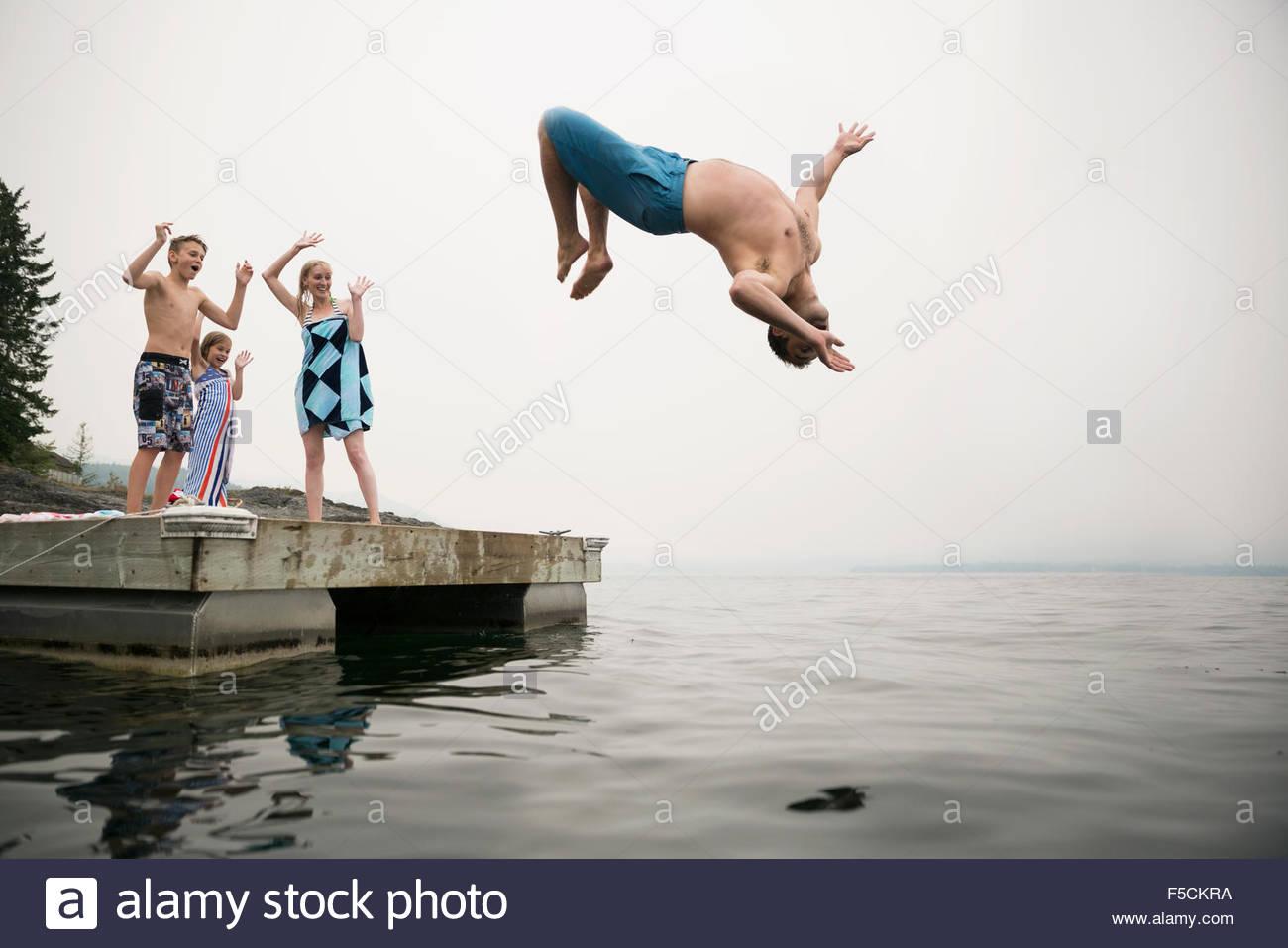 Famiglia tifo padre facendo backflip nel lago Immagini Stock