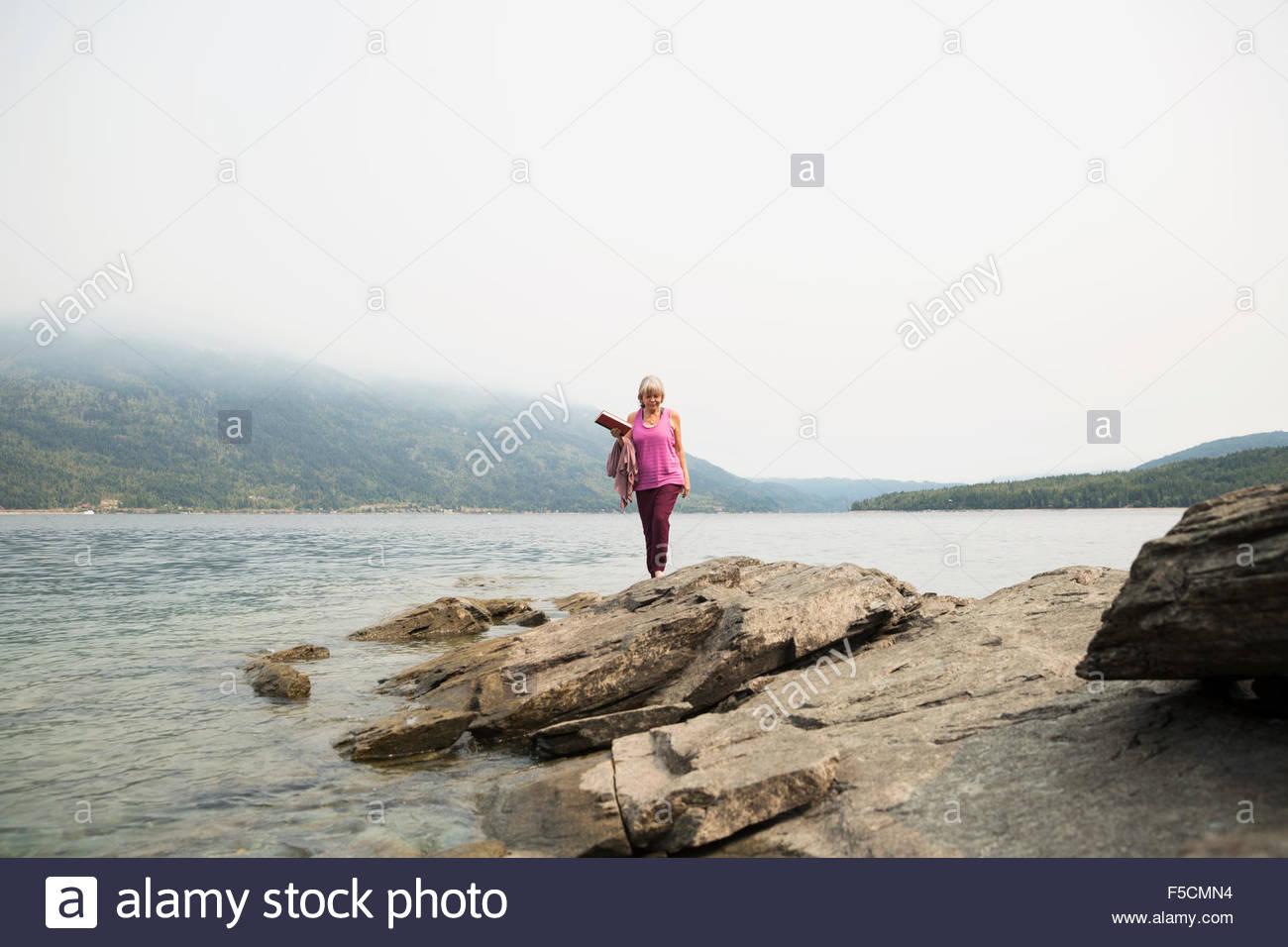 Donna che cammina sulle rocce a Lakeside Immagini Stock