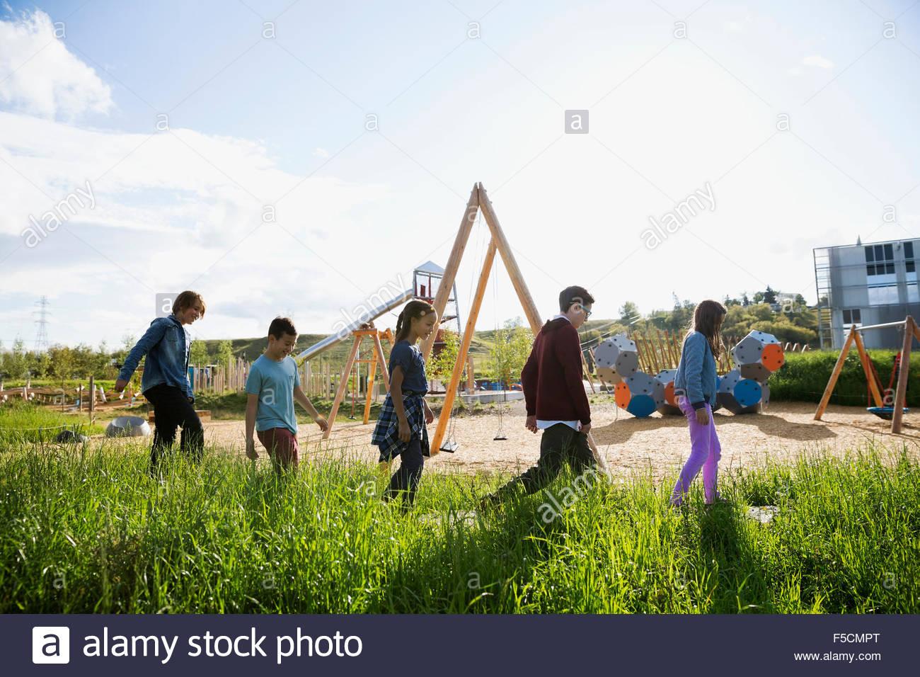 Bambini passeggiate lungo il soleggiato parco giochi Immagini Stock