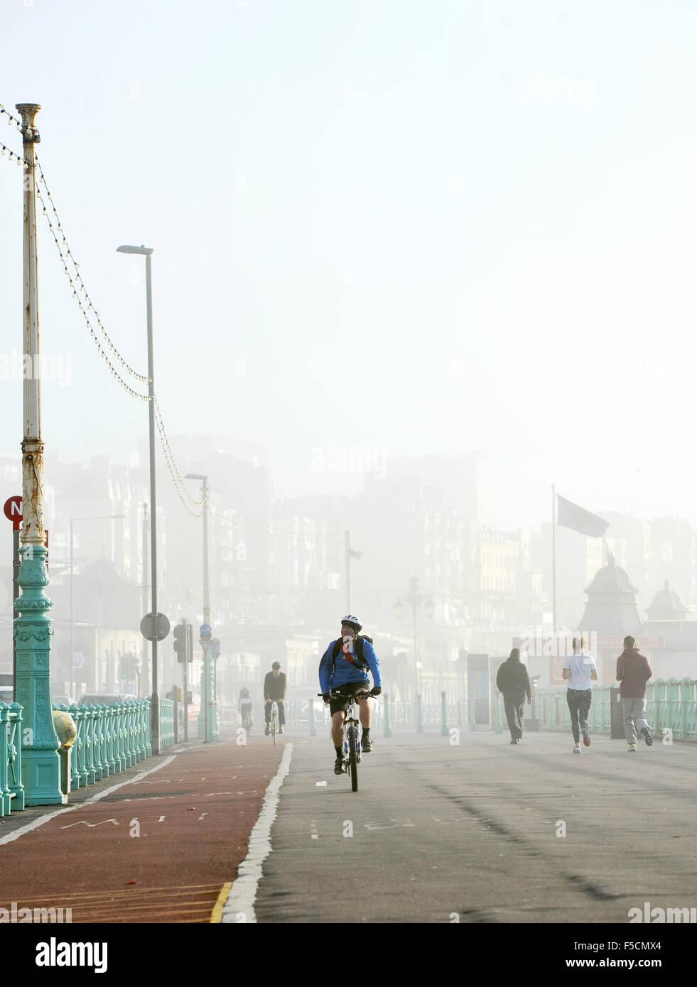 Brighton Sussex Regno Unito lunedì 2 novembre 2015 - i ciclisti e corridori non hanno problemi con i Foggy Immagini Stock