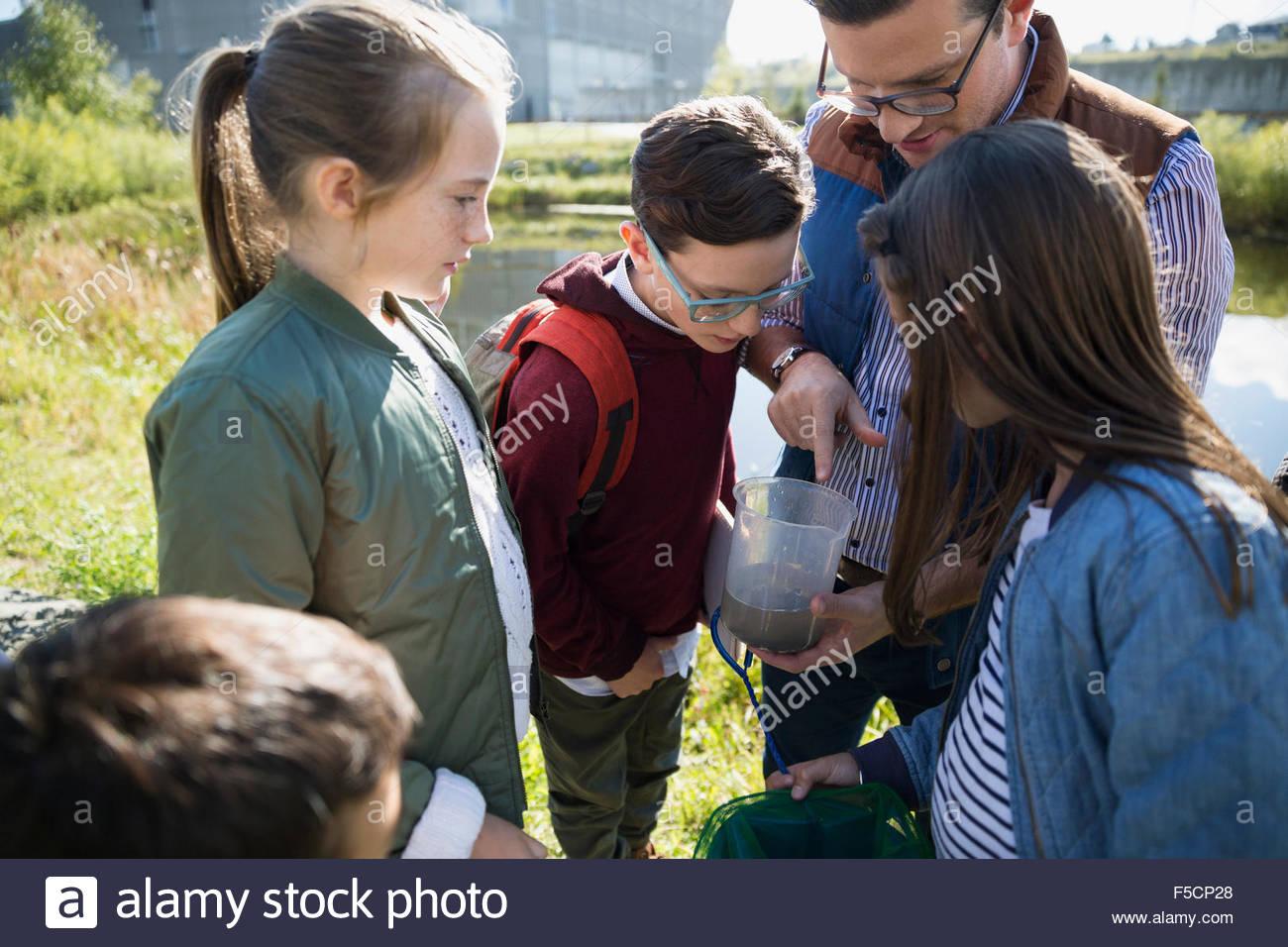 Insegnante di scienze e agli studenti di esaminare l'acqua Field Trip Immagini Stock