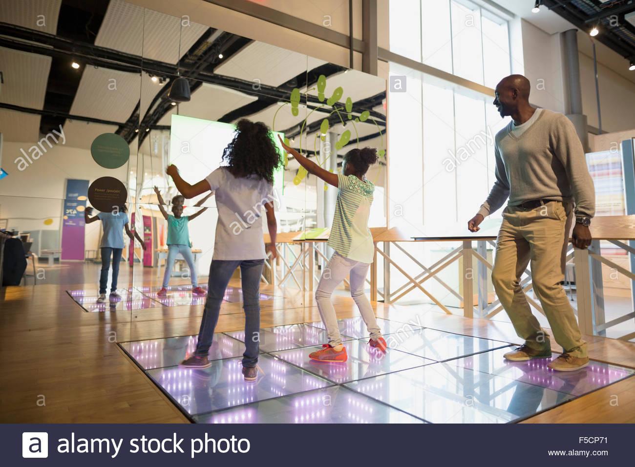 Padre guardando le figlie dance in science center Immagini Stock