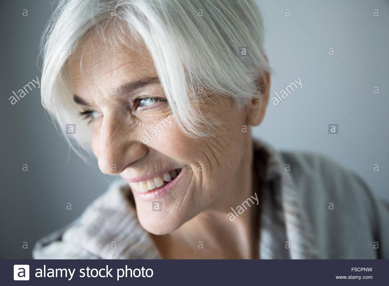 Chiudere fino a sorridere senior donna guardando sopra la spalla Immagini Stock