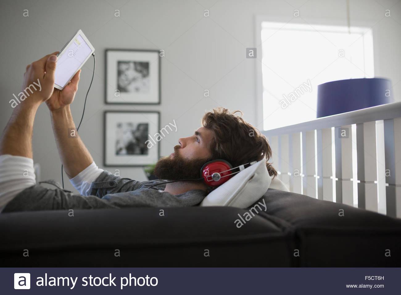 Uomo con tavoletta digitale Le cuffie per ascoltare musica Immagini Stock