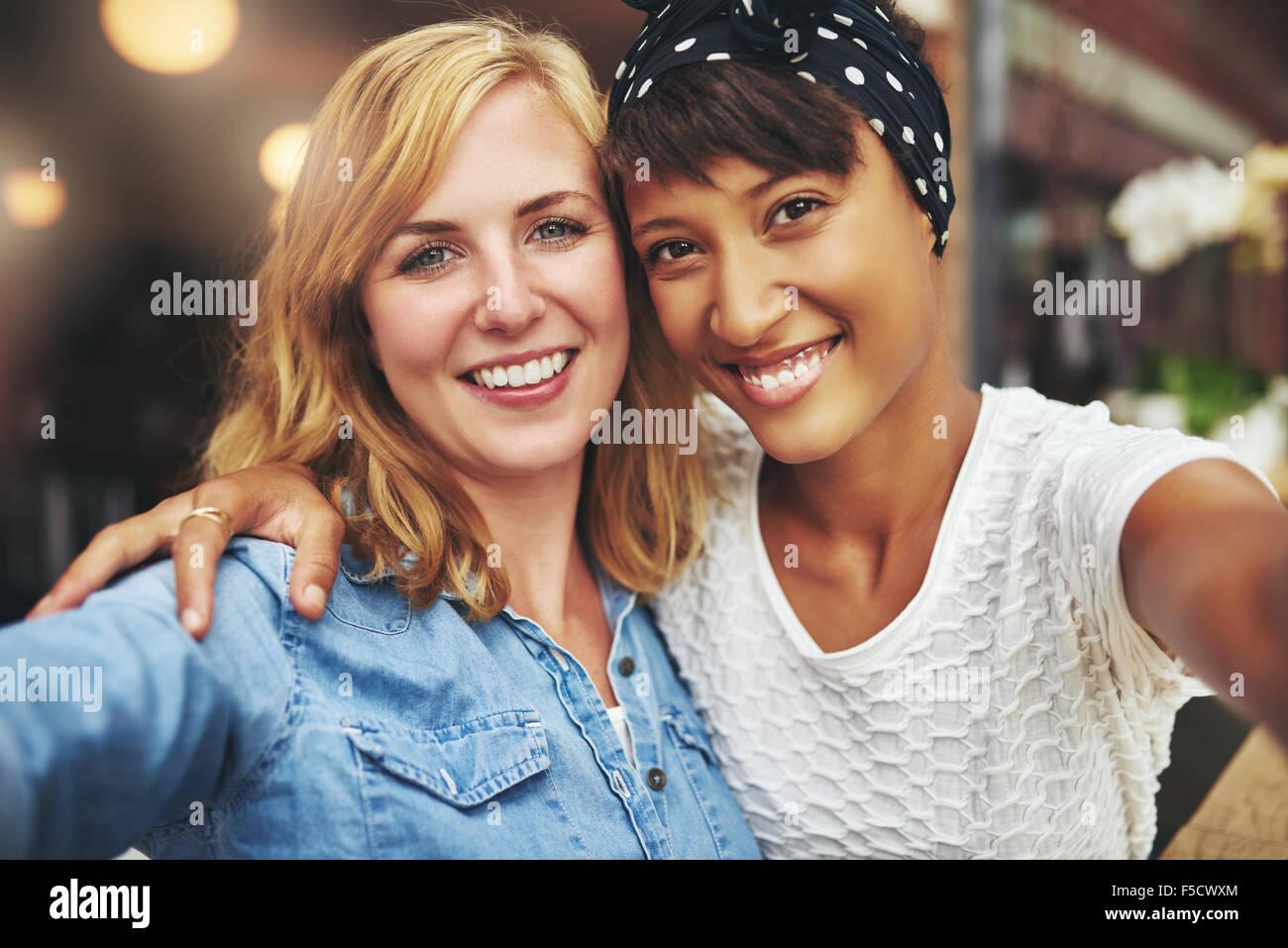 Due giovani donne migliori amici seduti a braccetto con le loro facce vicino insieme sorridente verso la telecamera, Immagini Stock