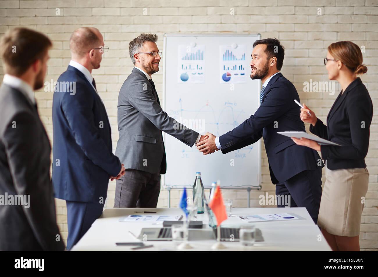 Soci stranieri saluto uno all'altro mediante le procedure di handshaking Immagini Stock