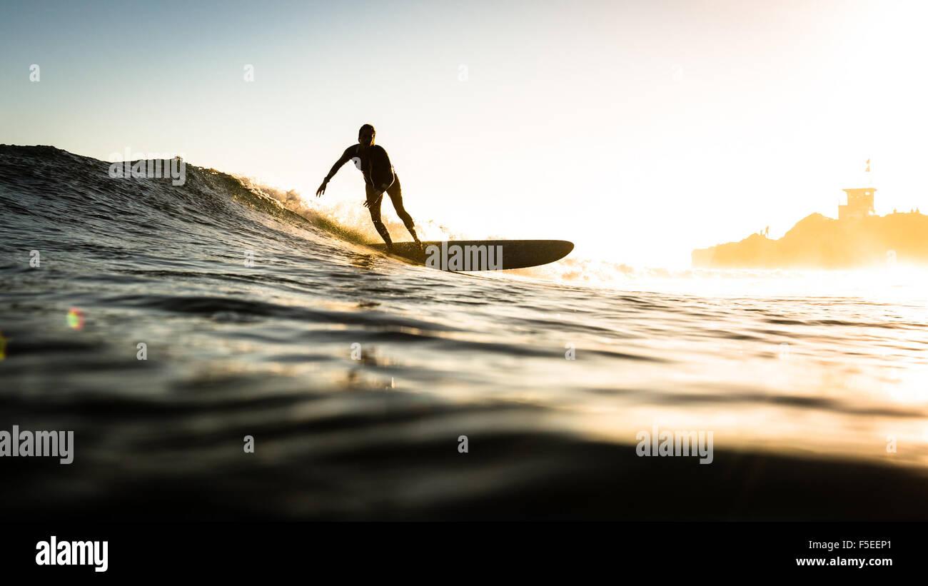 Donna surf al tramonto, Malibu, California, Stati Uniti d'America Immagini Stock