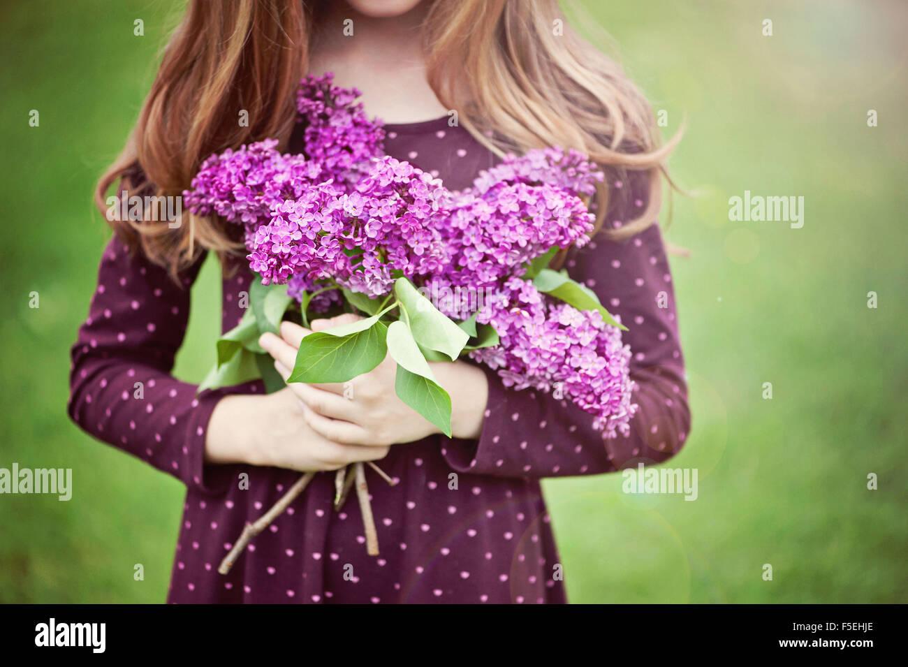 Close-up di una ragazza con mazzo di fiori lilla Immagini Stock