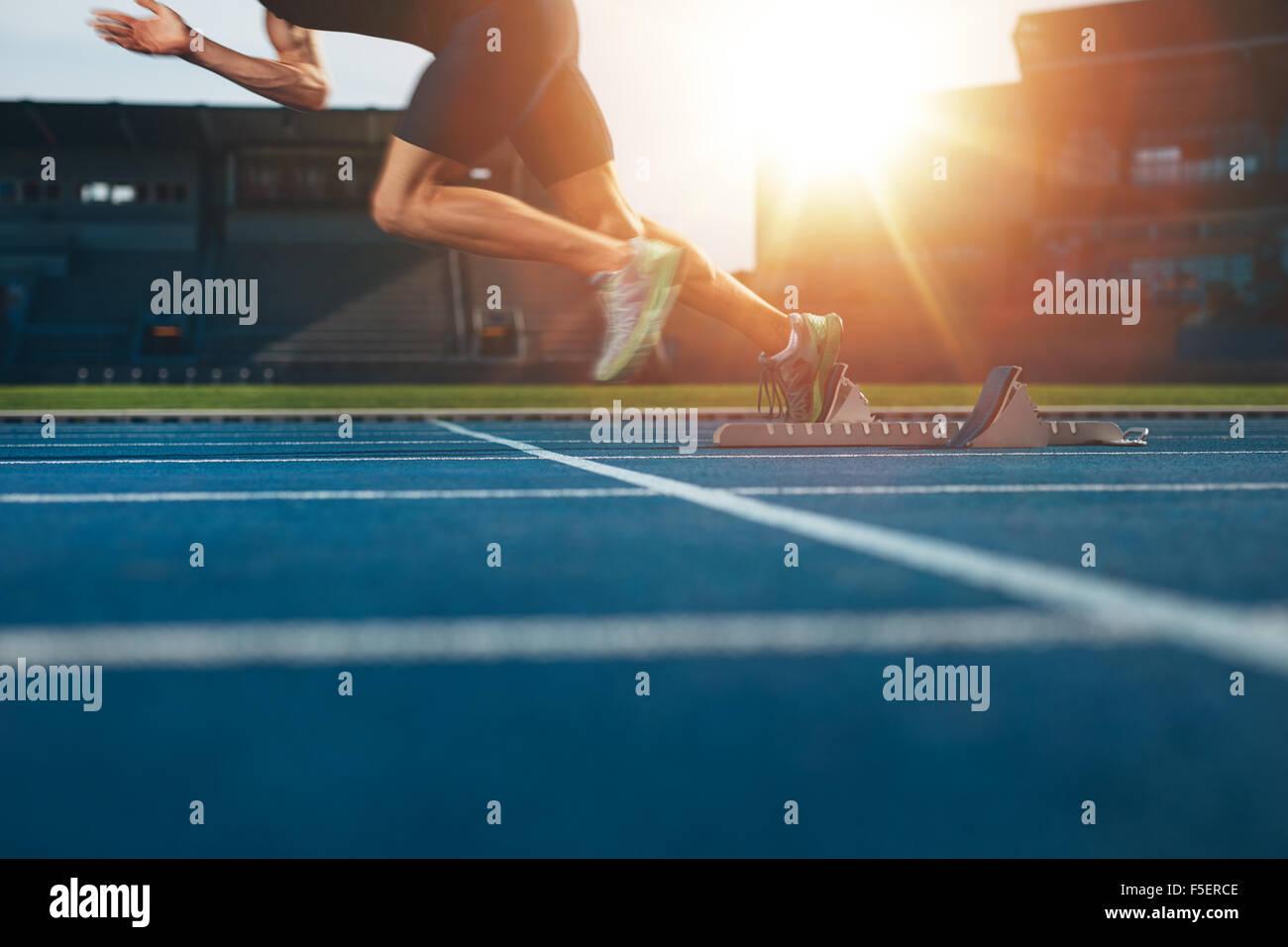 Atleta che corre sulla pista di atletica. Sezione bassa shot dei maschi di runner la partenza sprint dalla linea Immagini Stock