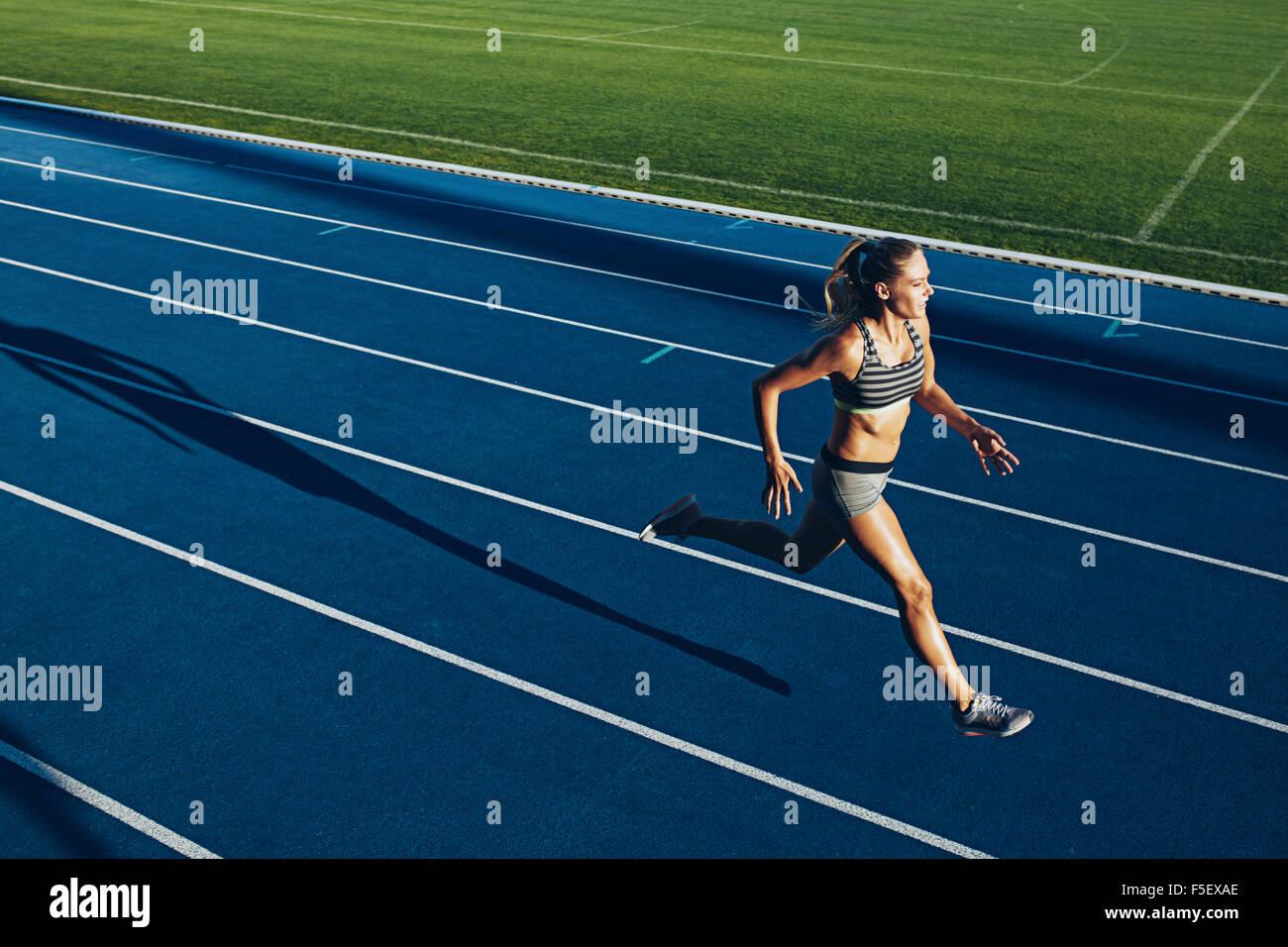 Giovane donna in esecuzione su pista durante la sessione di formazione. Guida femmina pratica sulla pista di atletica Immagini Stock