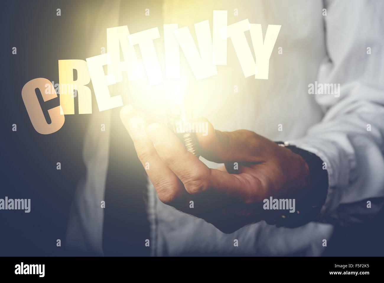 Il concetto di creatività con imprenditore tenendo lampadina, dai toni rétro immagine, il fuoco selettivo. Immagini Stock