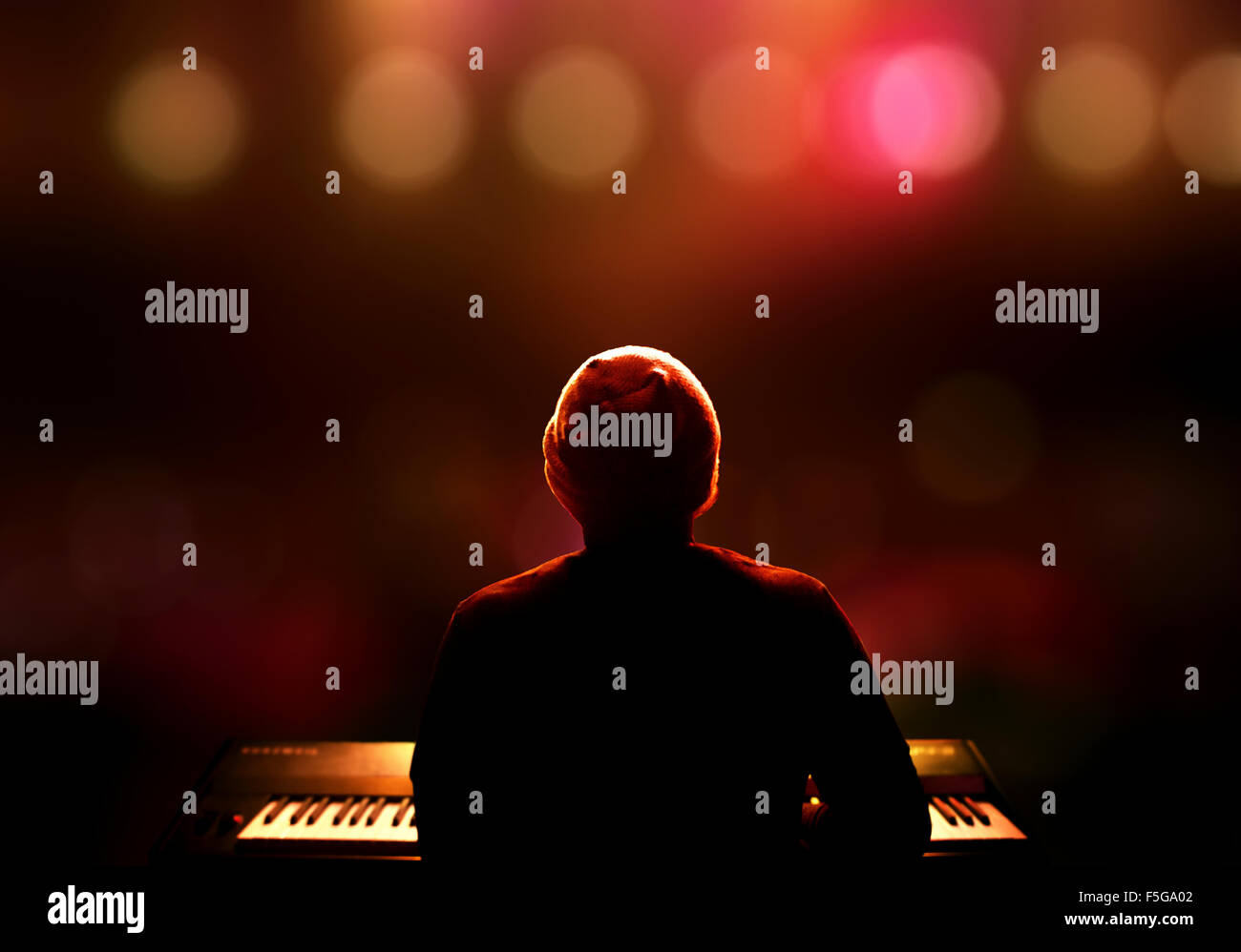 Pianista che suona il sintetizzatore dal vivo sul palco. Visto da dietro con estrema DOF poco profondo Foto Stock