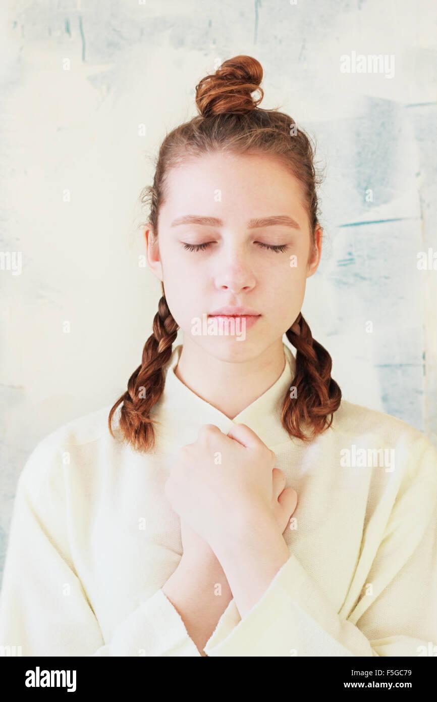 La tranquilla ragazza sta con gli occhi chiusi e le mani giunte Immagini Stock