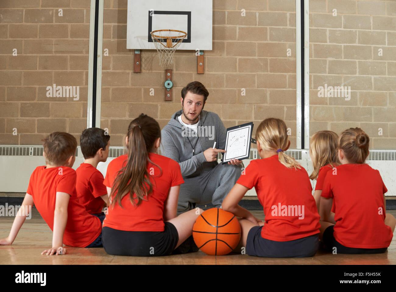 Allenatore dando Team parlare alla scuola elementare della squadra di basket Immagini Stock