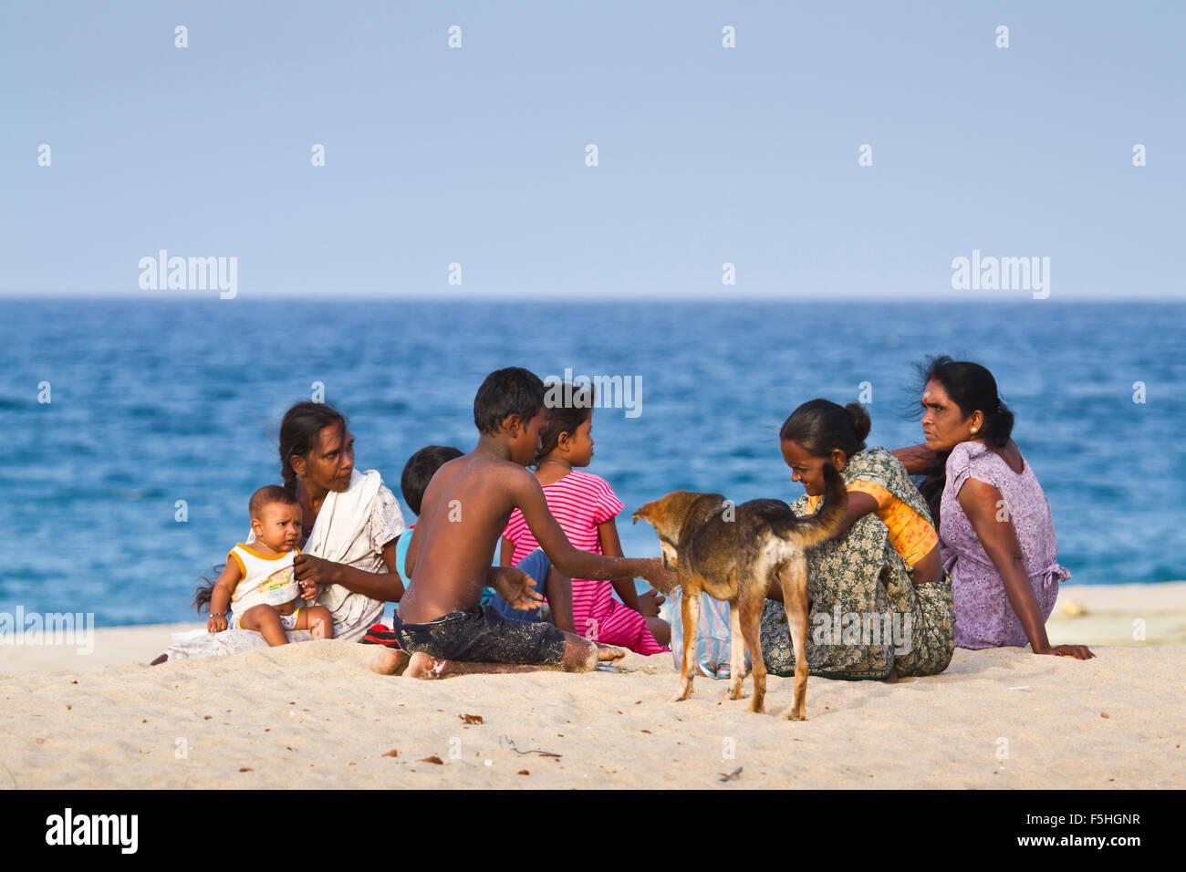Tamul tradizionale famiglia avente il resto nel distretto di Batticaloa beach, Sri Lanka Immagini Stock
