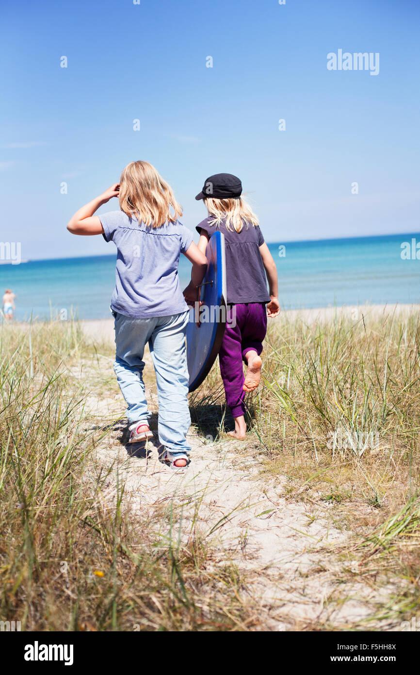 La Svezia, Gotland, Faro, due ragazze (8-9, 10-11) passeggiate sulla spiaggia Immagini Stock