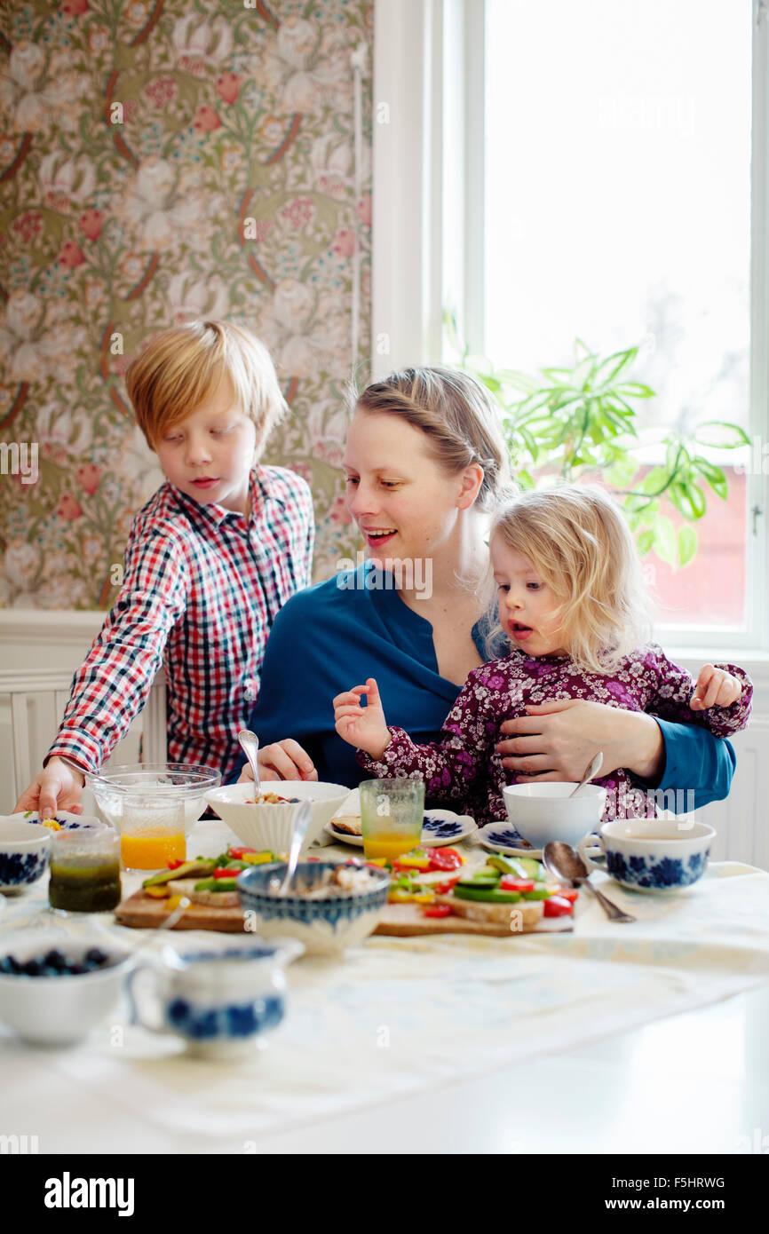La Svezia, madre di due bambini (2-3, 10-11) di mangiare la prima colazione Immagini Stock