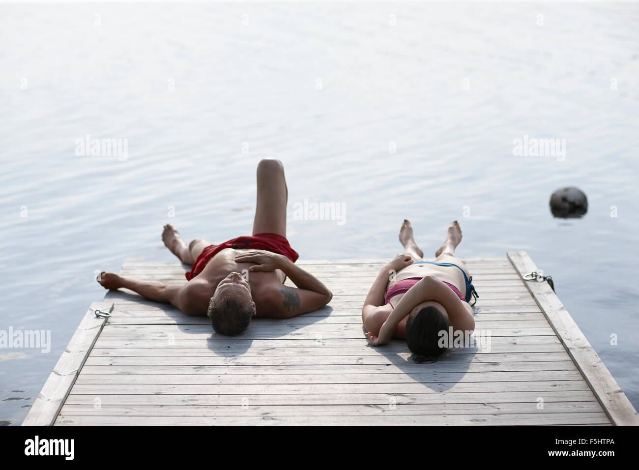 La Svezia, Dalarna, Siljan, l uomo e la donna sdraiata sul molo Immagini Stock
